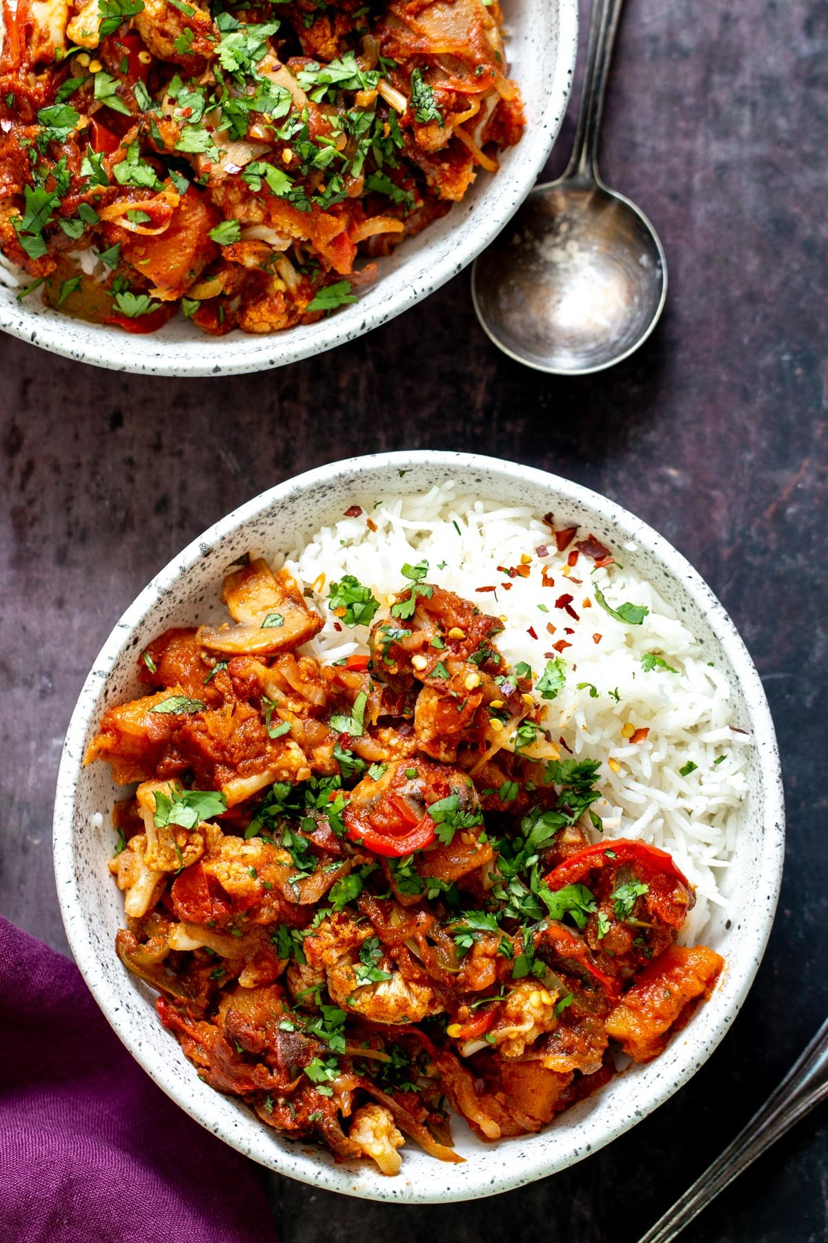 a bowl of vegetable balti served with rice and sprinkled with fresh parsley