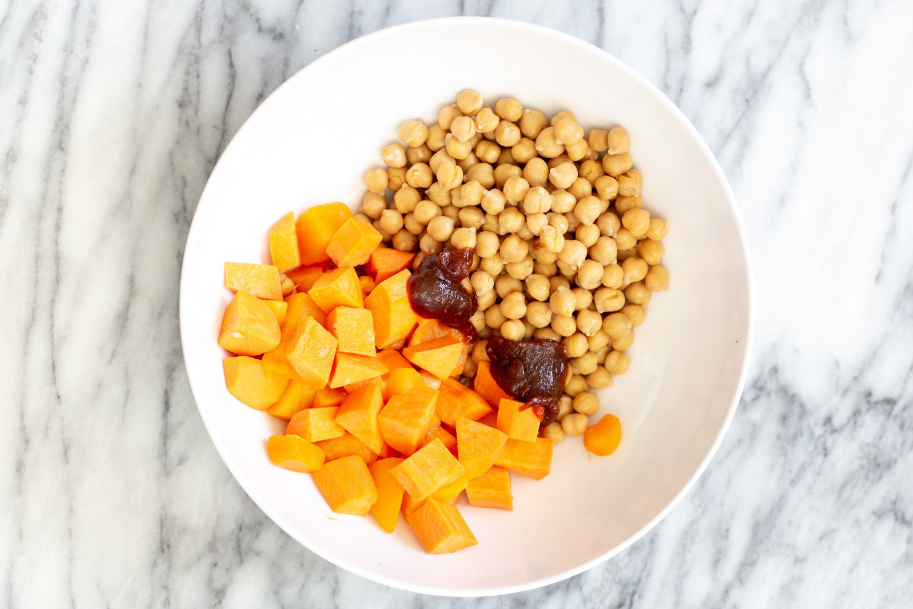 sweet potatoes and chickpeas in a bowl with some bbq sauce