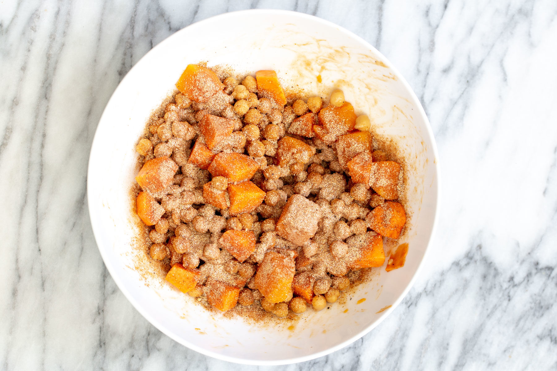 spice mix being sprinkled on top of sweet potatoes and chickpeas