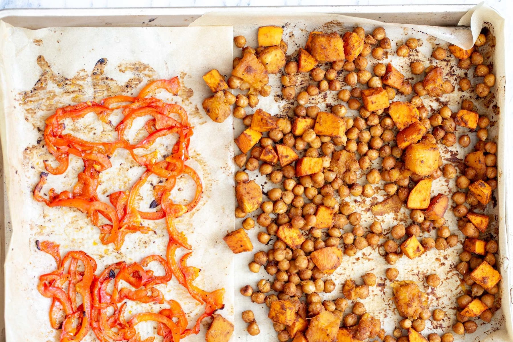 chickpeas, sweet potatoes and sliced red bell peppers being baked on a sheet pan for vegan salad bowl recipe