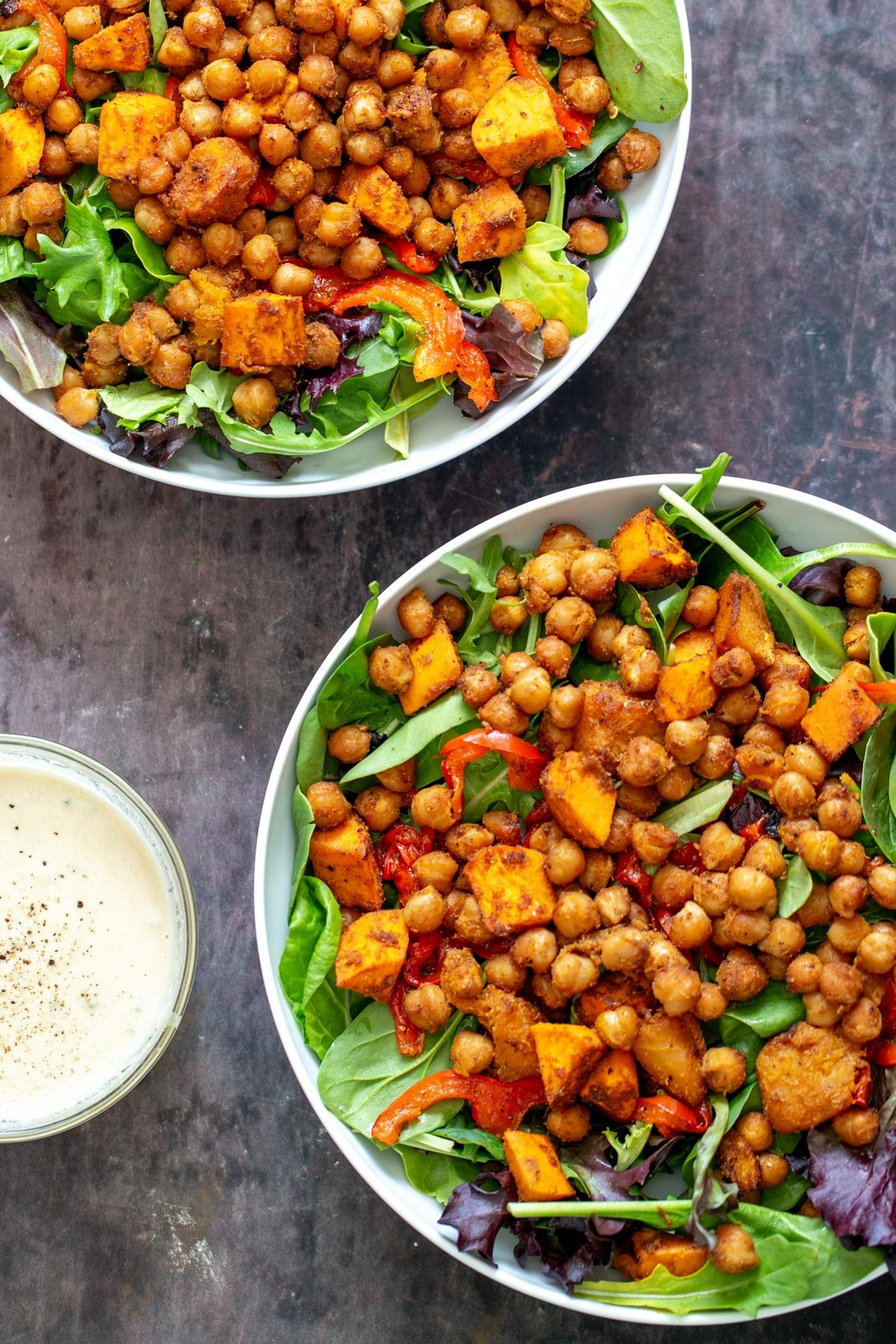 two bowls with salad topped with baked chickpeas and roasted bell pepper and sweet potatoes with a small dish of tahini dressing on the side
