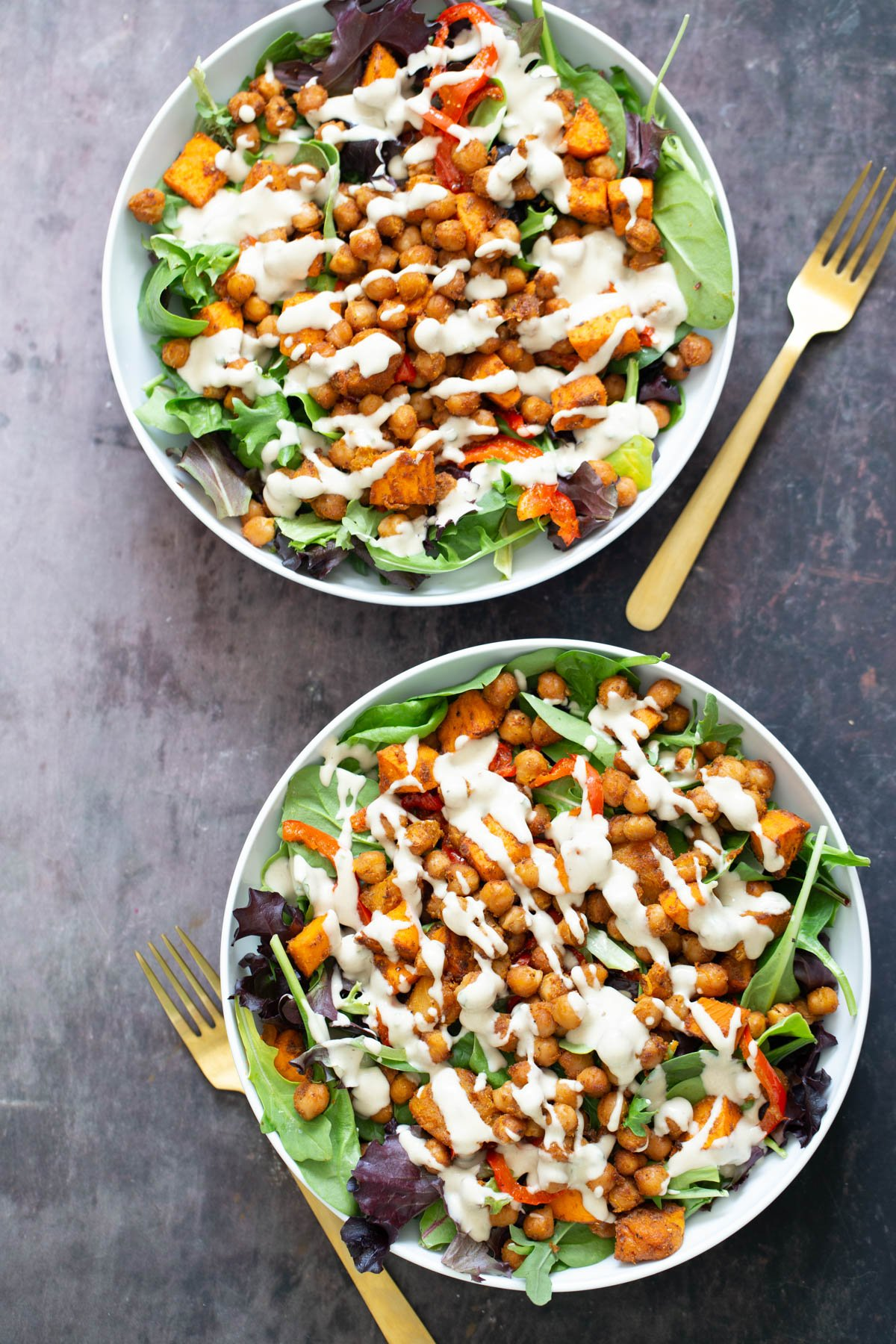sweet potato chickpea salad served in two white bowls drizzled with tahini dressing