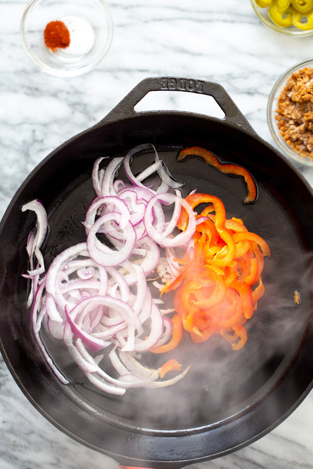 onions and bell pepper sauteeing in a skillet