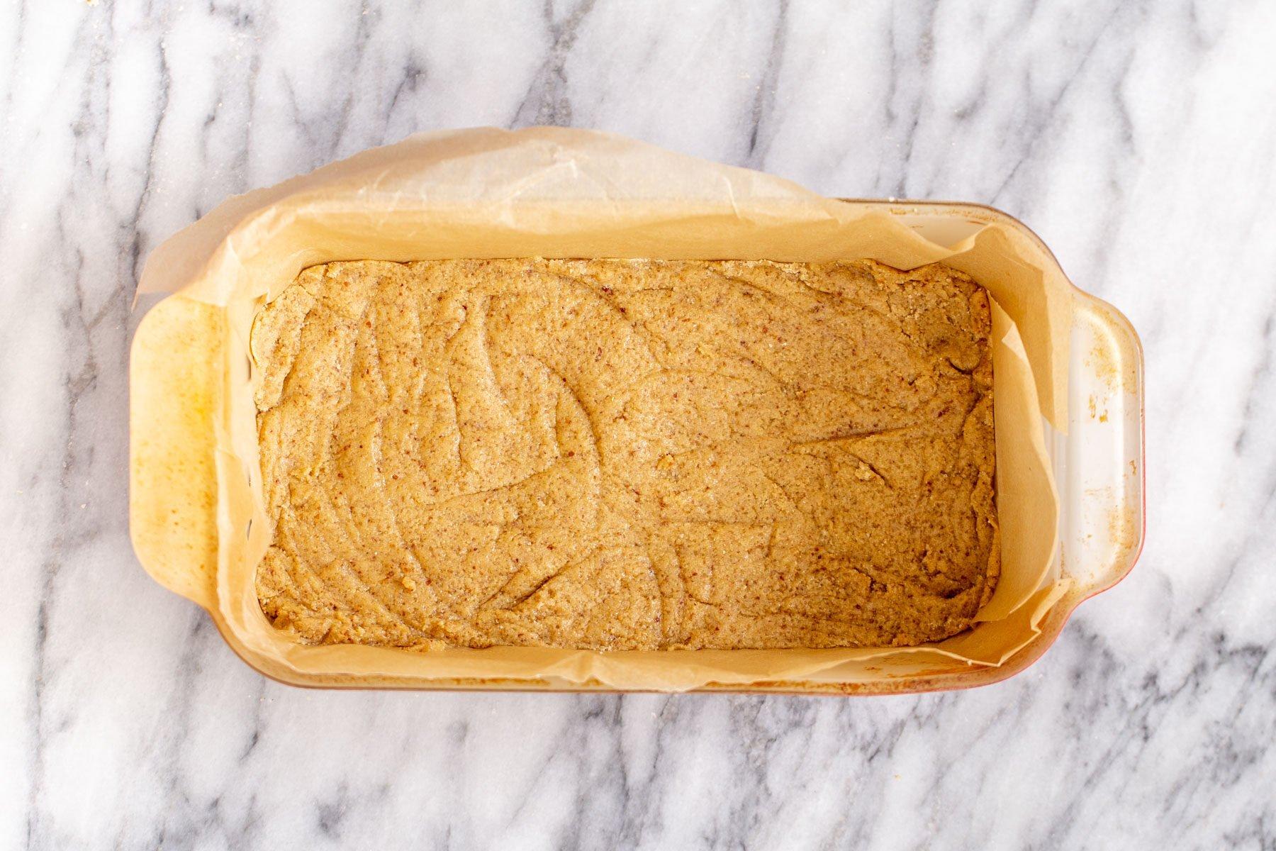 vegan cookie crust pressed in a pyrex loaf pan