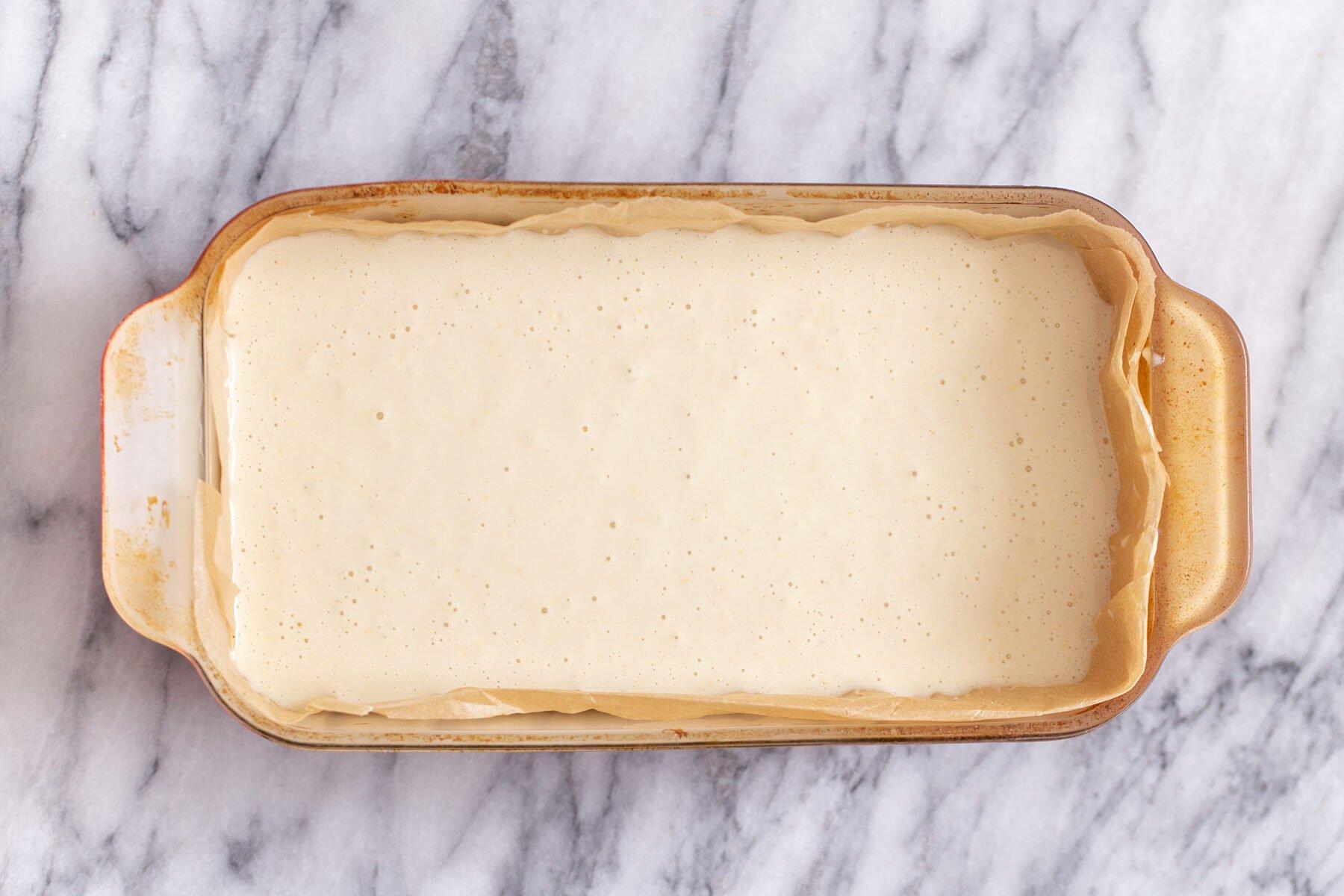 vegan lemon cream filling being poured in a pyrex loaf pan to make lemon bars
