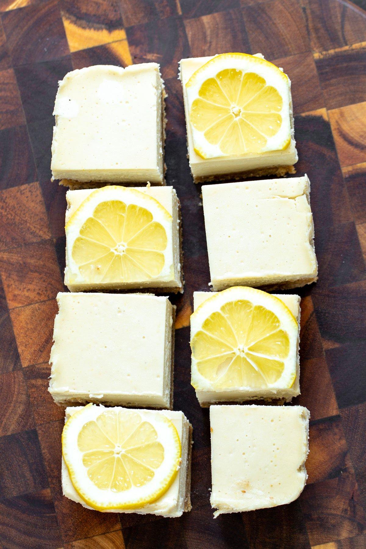 vegan lemon bars on a wooden chopping board topped with lemon slices