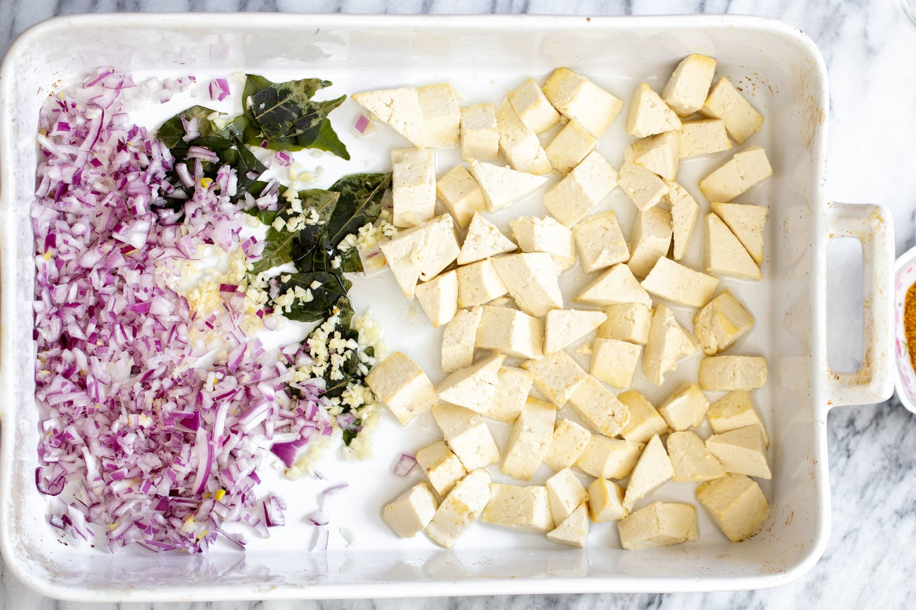 a casserole dish with cubed tofu, chopped onions and curry leaves