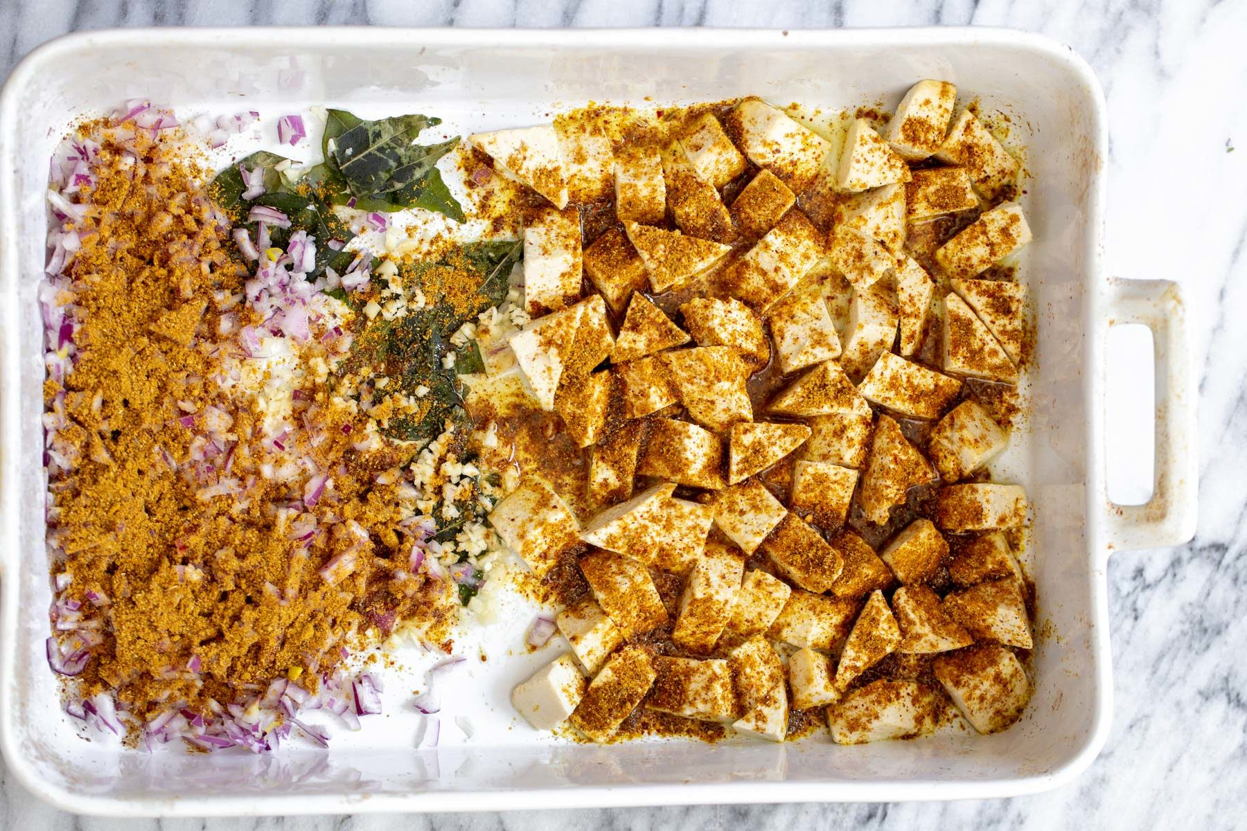 tofu, onions and curry leaves in a casserole dish sprinkled with madras curry powder