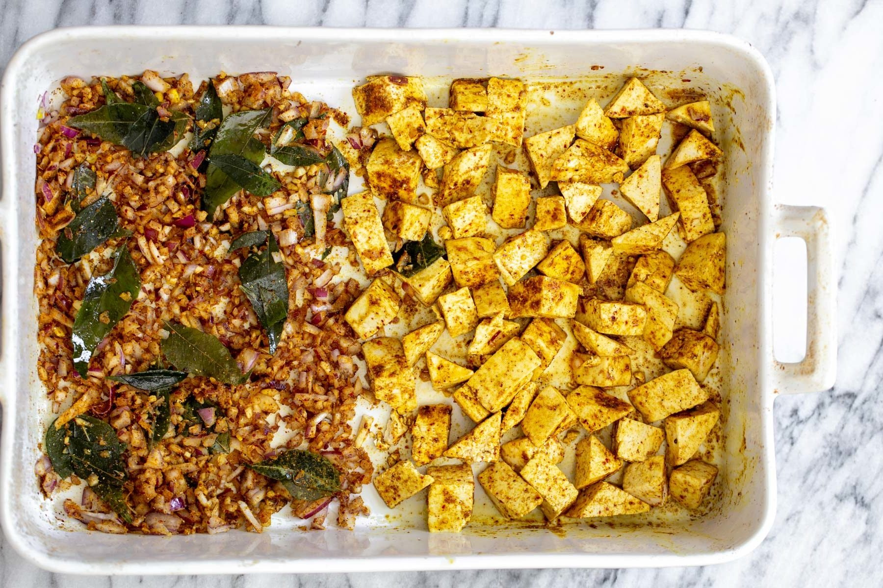 casserole dish with curry spiced baked tofu and onions
