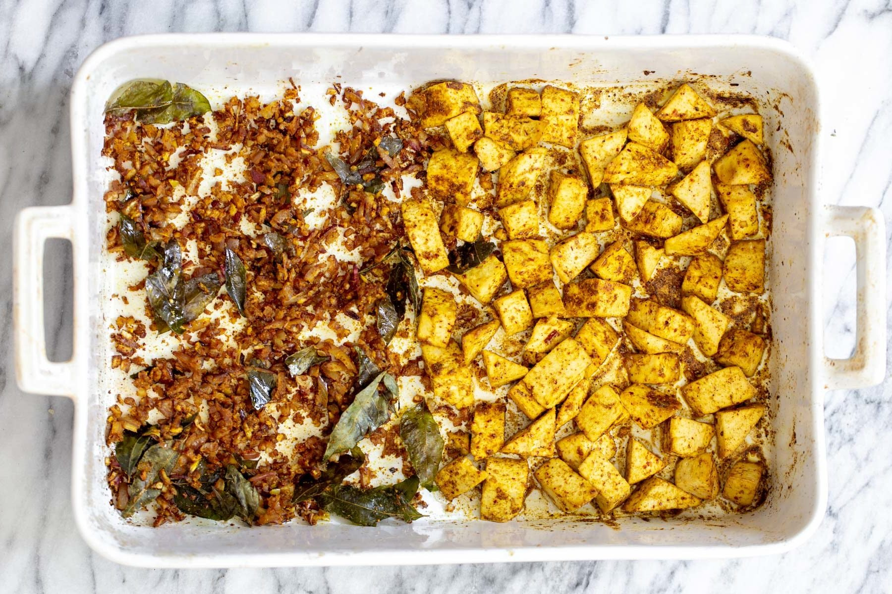 casserole dish with spiced baked tofu on one side and onions on the other side