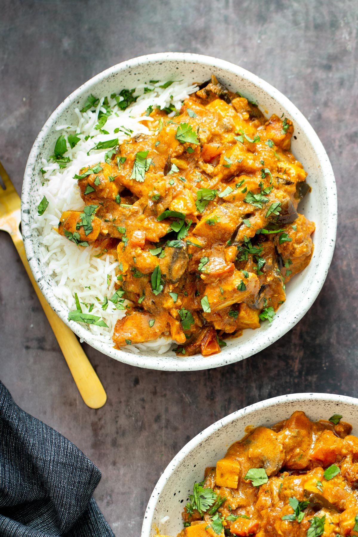 a serving of rich Indian Madras Curry tofu casserole served with rice and fresh cilantro