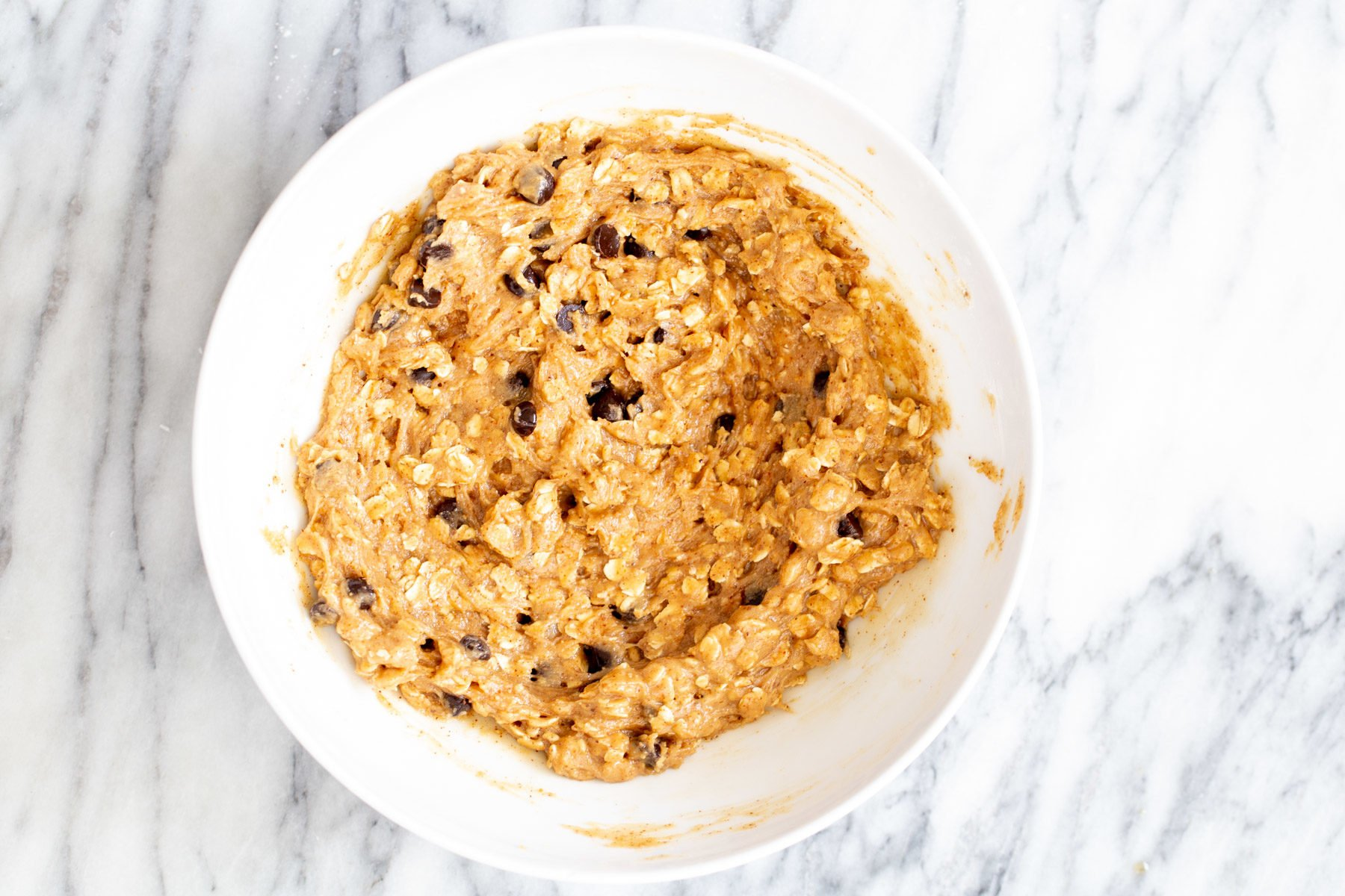 vegan carmelita oatmeal batter with chocolate chips in a mixing bowl