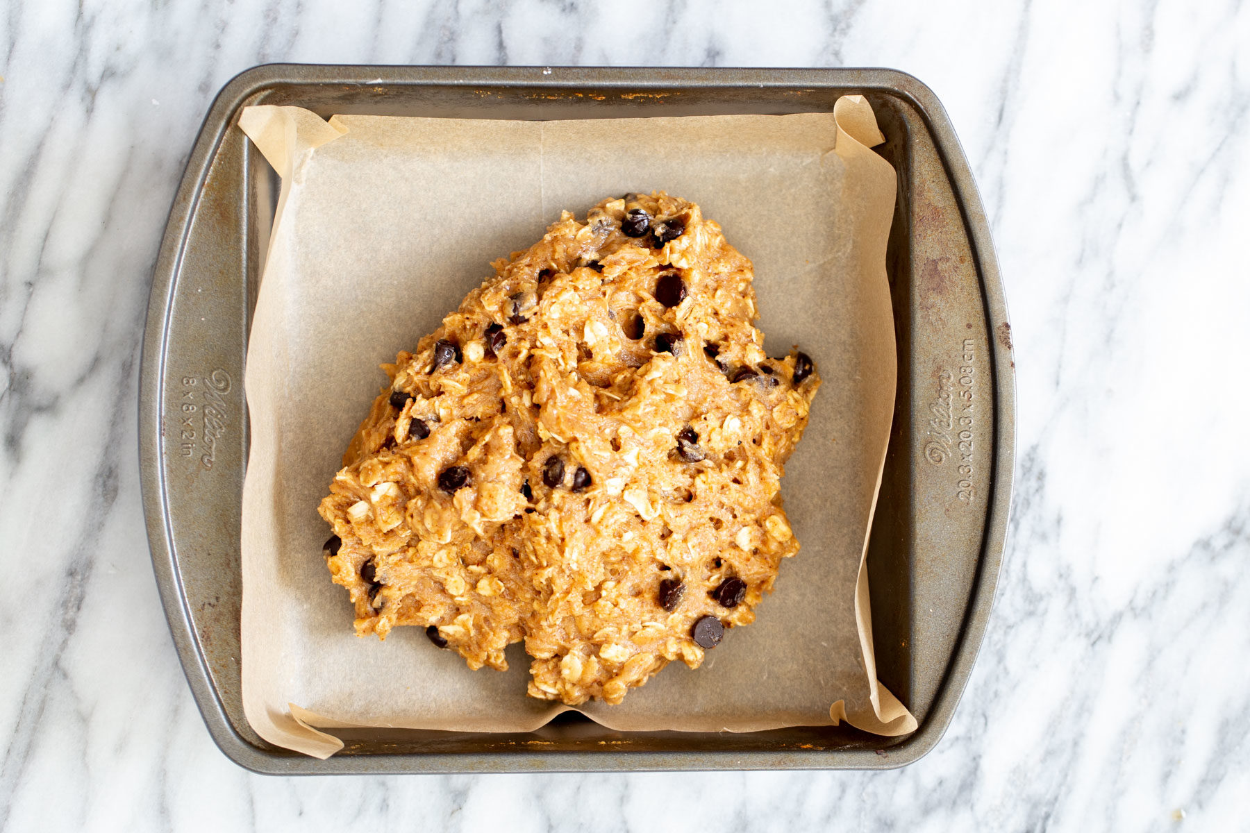 vegan date caramel oatmeal bar batter being added to a square baking pan