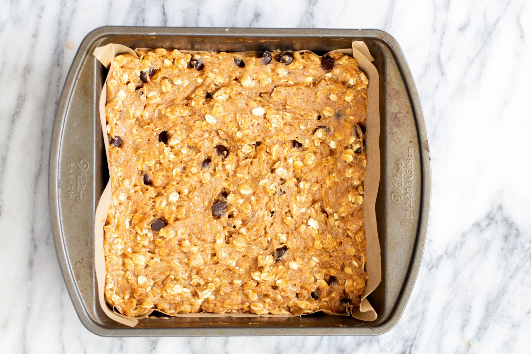 oatmeal bar batter in a square brownie pan