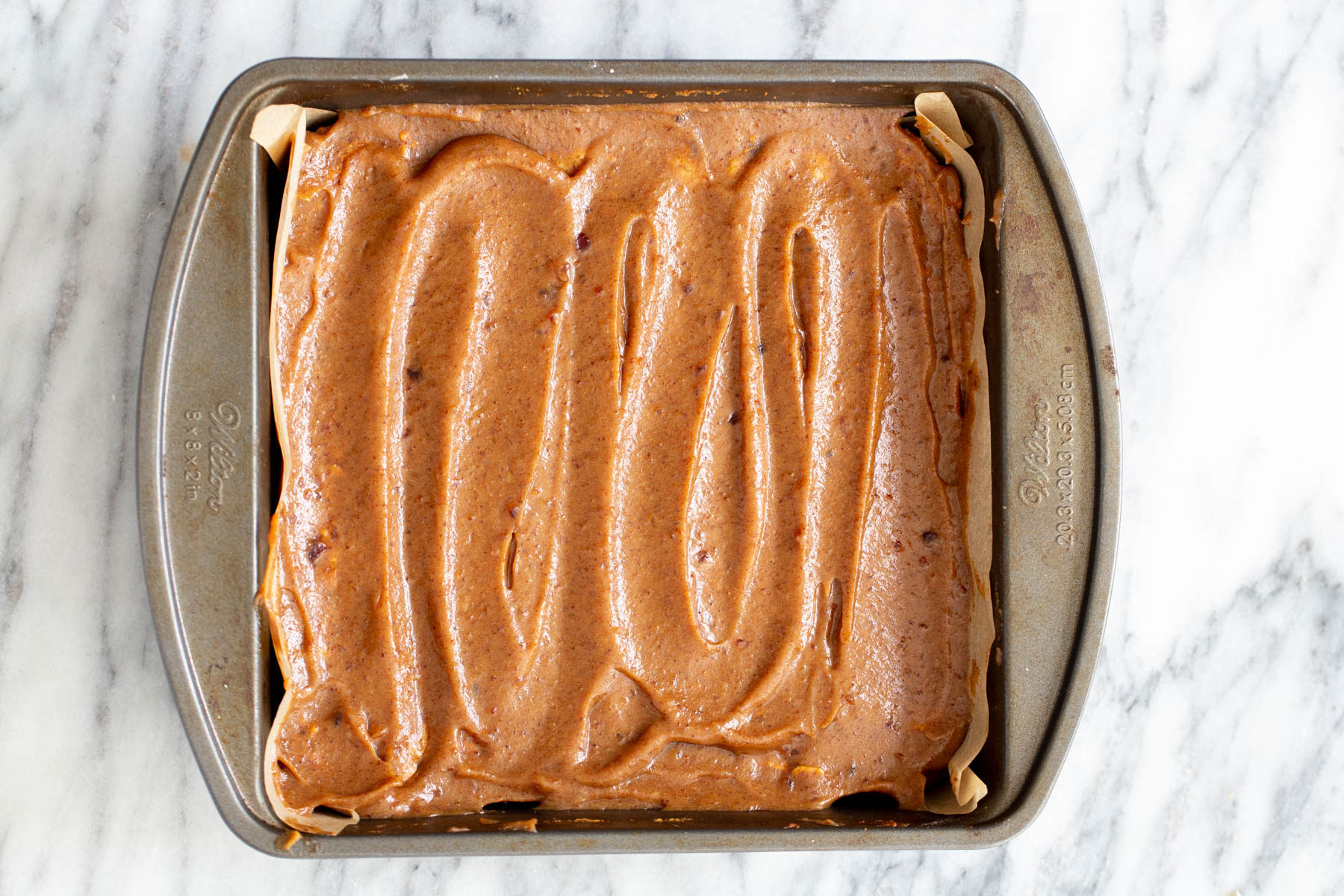 vegan date caramel being spread on oatmeal batter to make vegan date caramel oatmeal bars