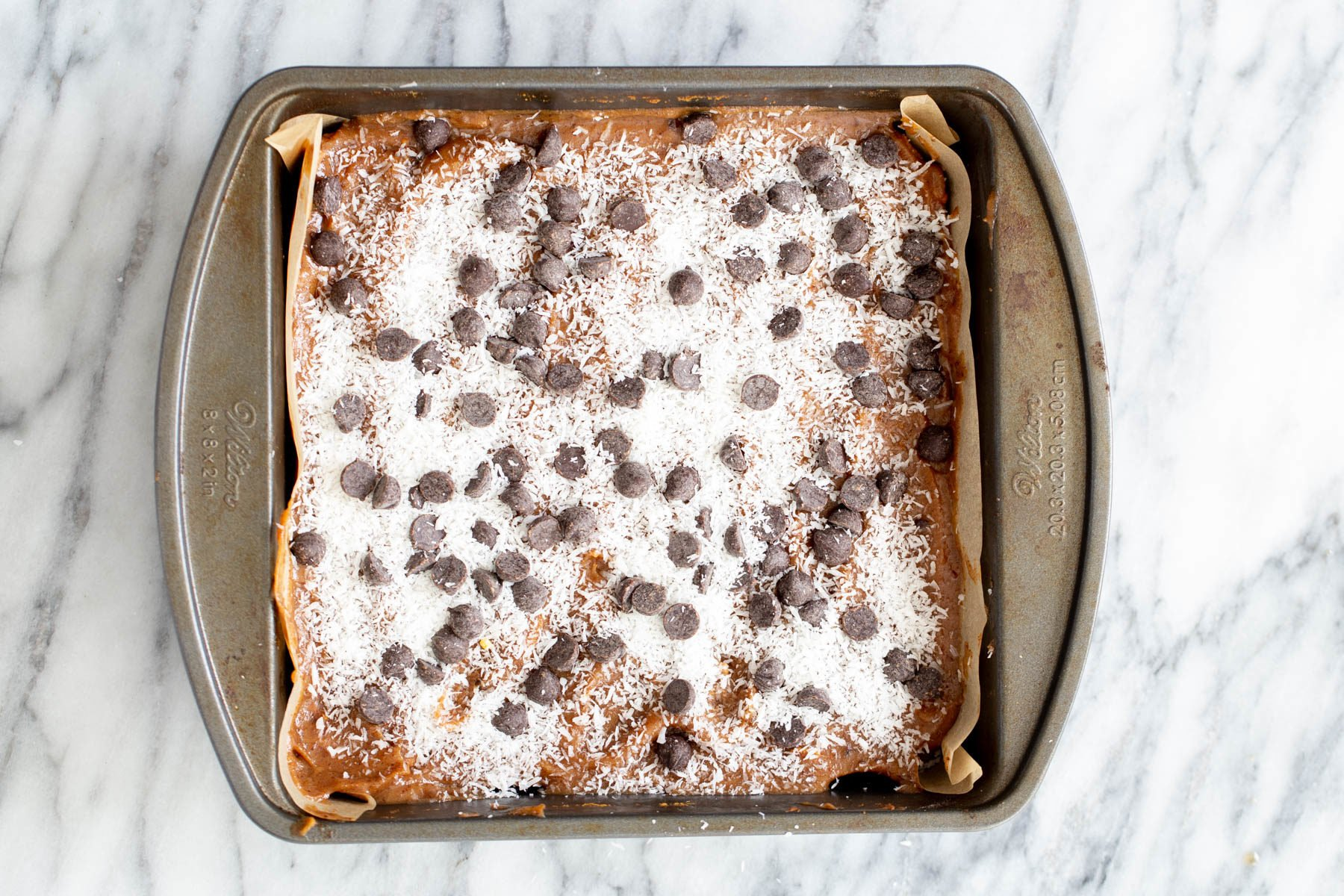 chocolate chips and shredded coconut being spread on top of oatmeal cookie base and date caramel to make caramel bars