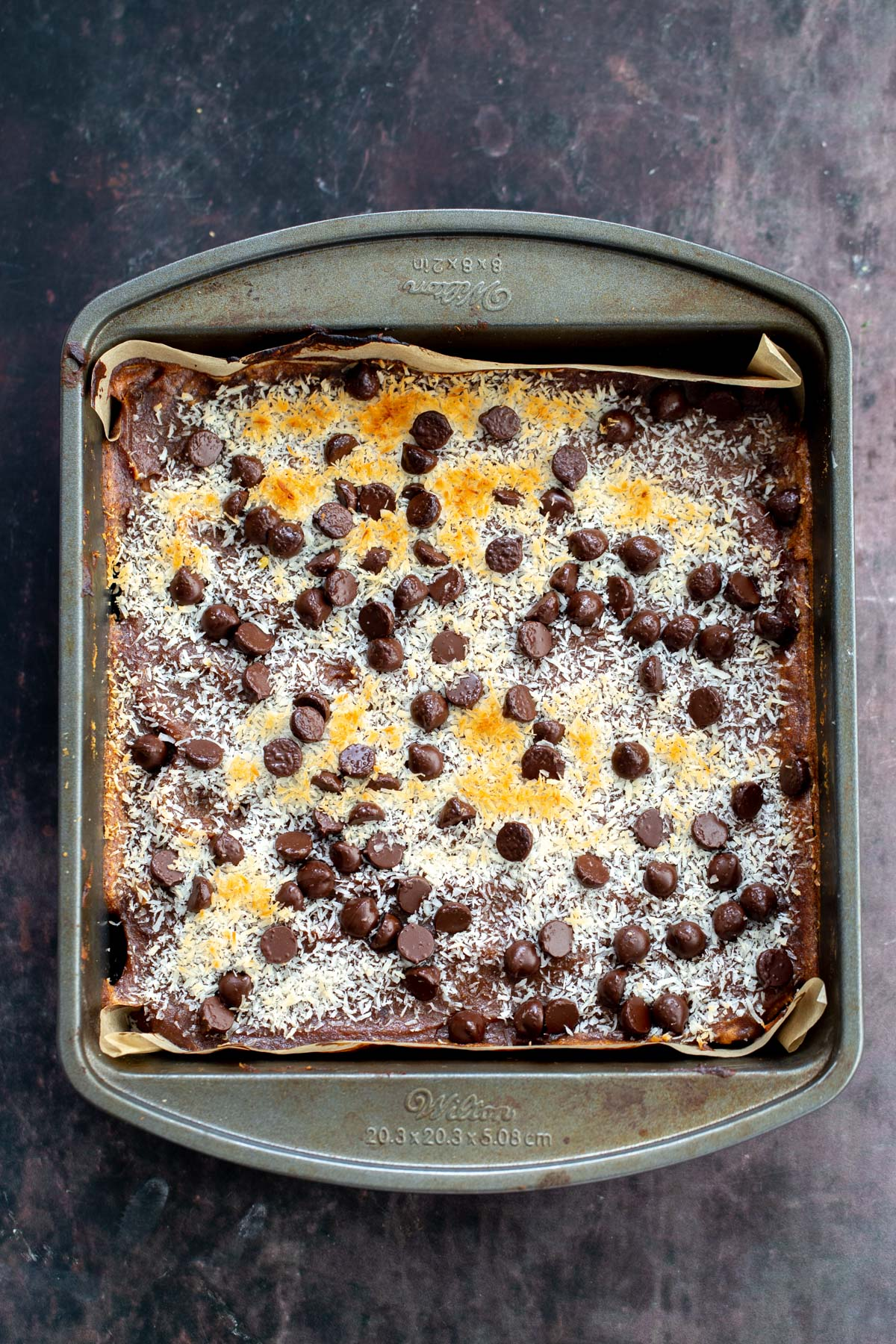 freshly baked vegan carmelita oatmeal caramel bars in a baking pan