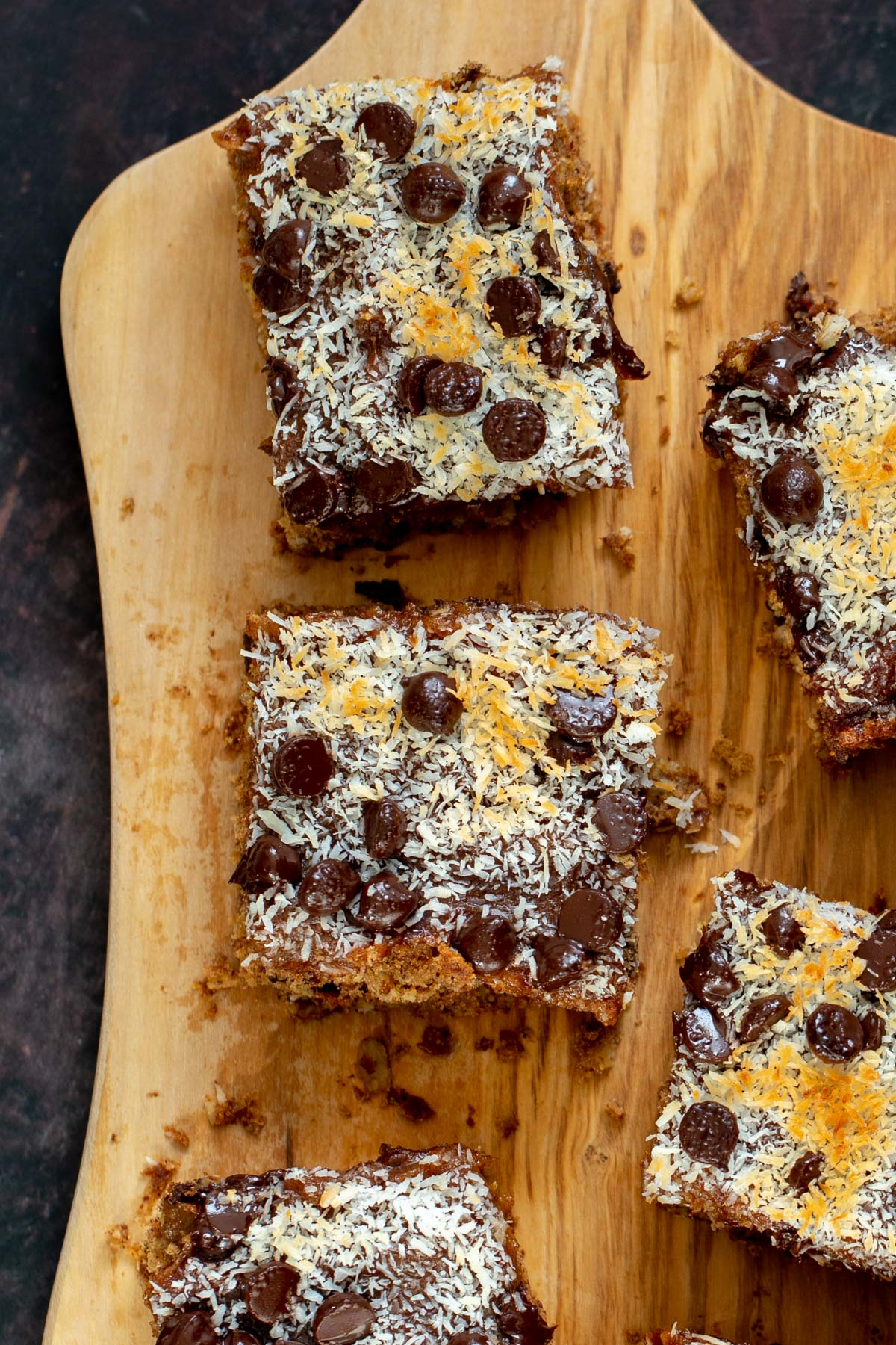 vegan oatmeal date caramel snack bars topped with shredded coconut and chocolate chips on a cutting board