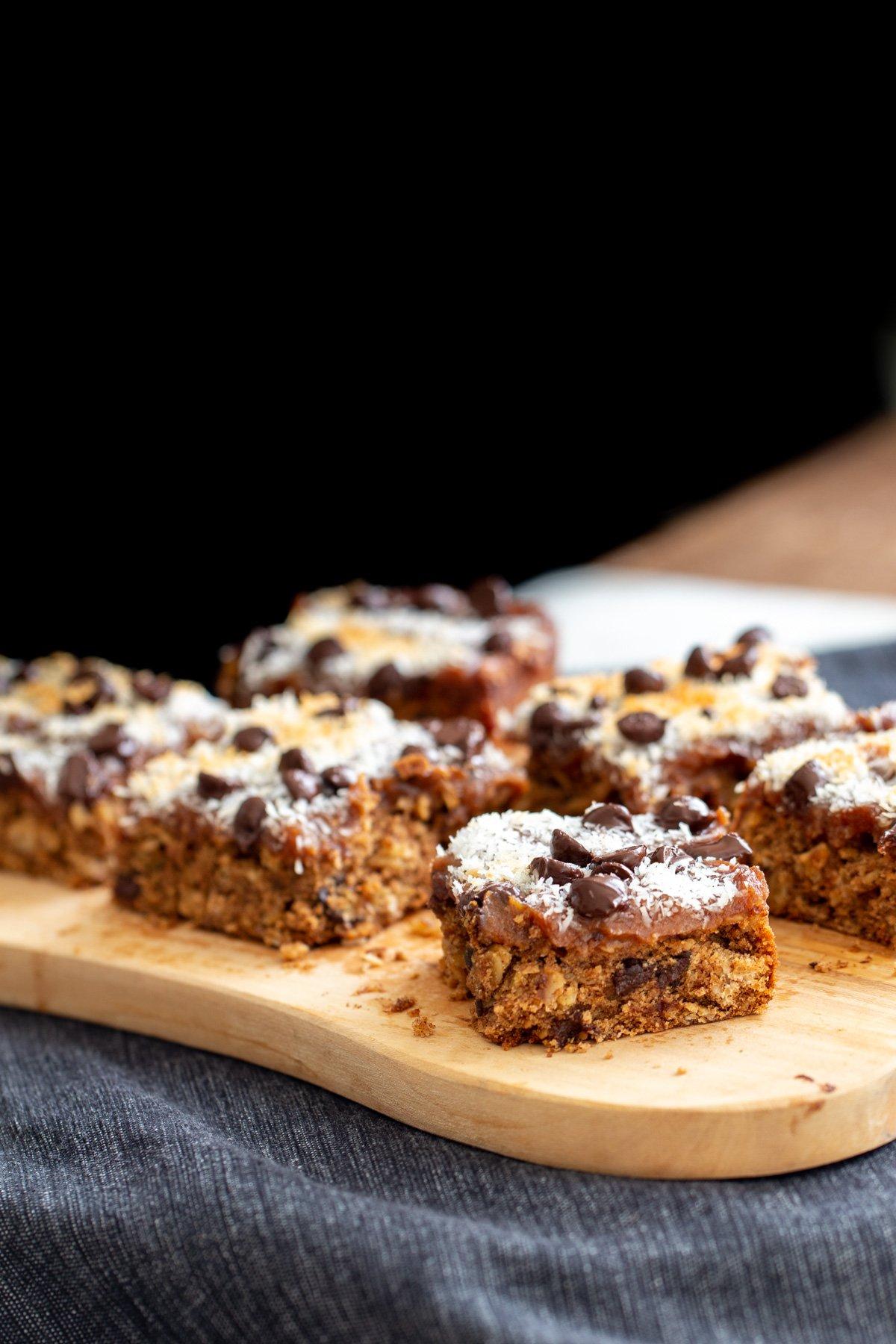 vegan oatmeal date caramel bars on a wooden board
