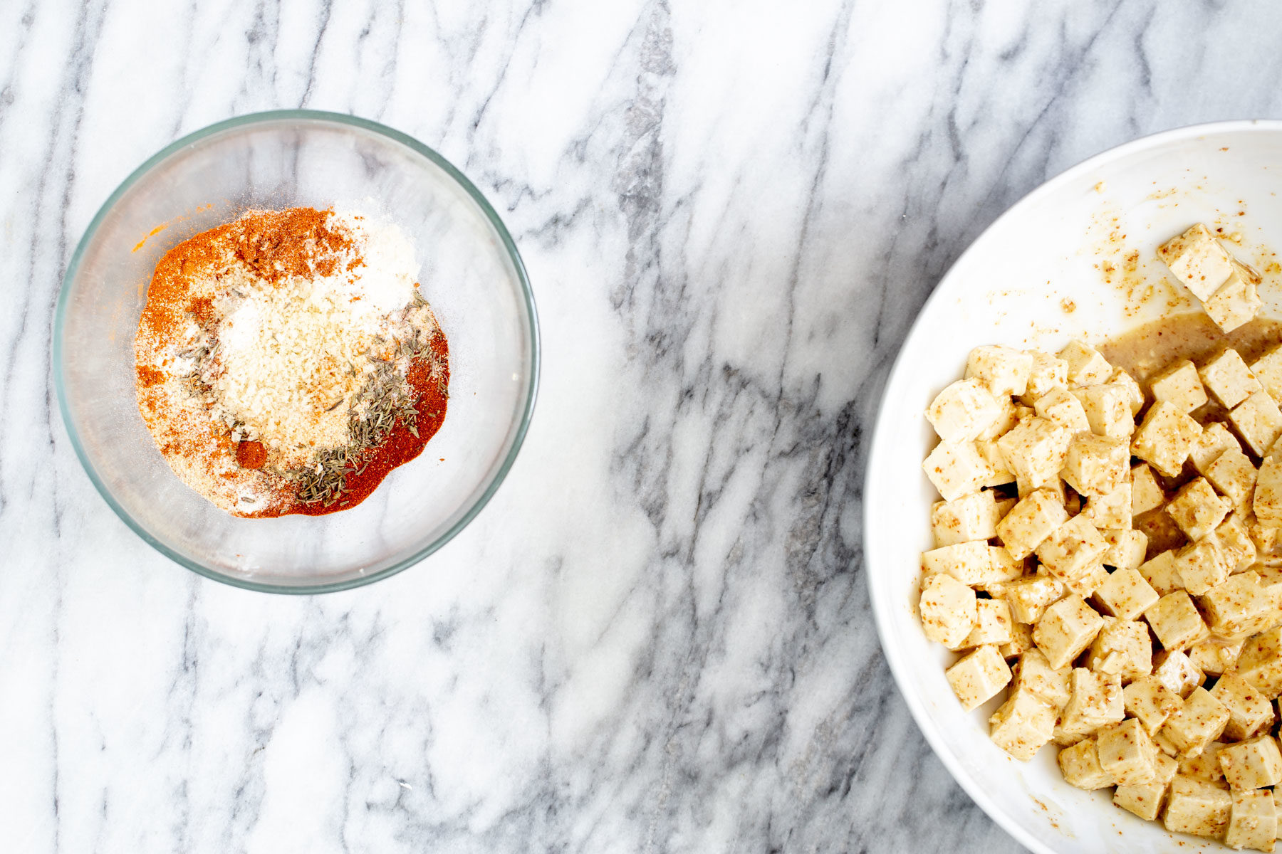 a bowl with marinated tofu and a bowl with spice mix on a marble countertop