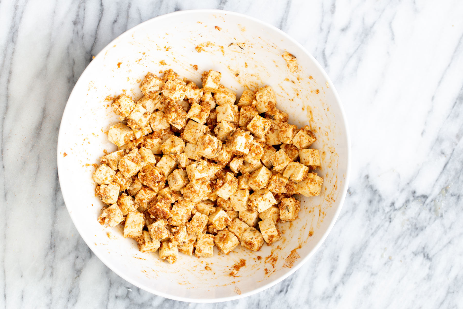 marinated cubed tofu being mixed with crunch topping