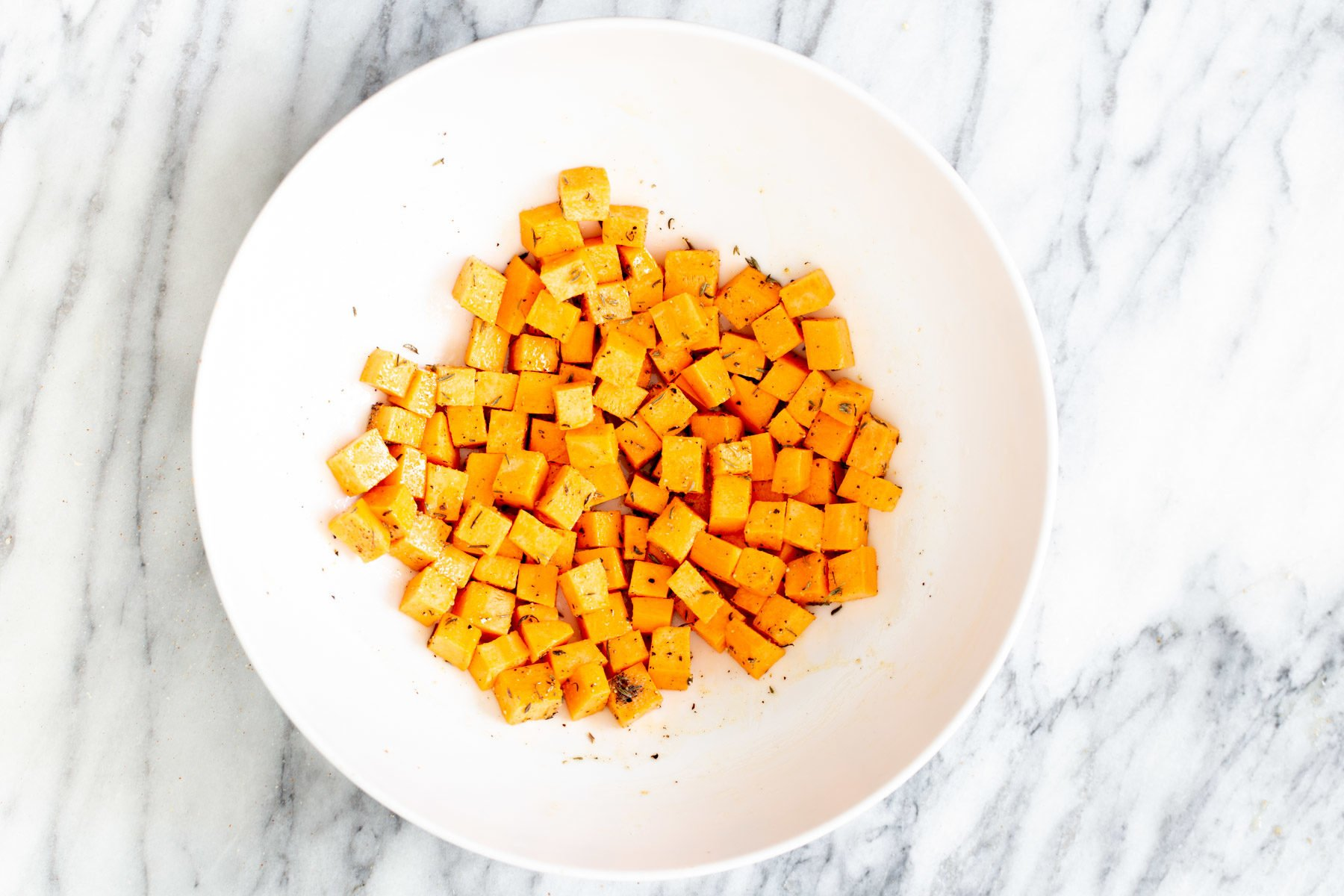 sweet potato cubes mixed with seasoning and oil in a small bowl