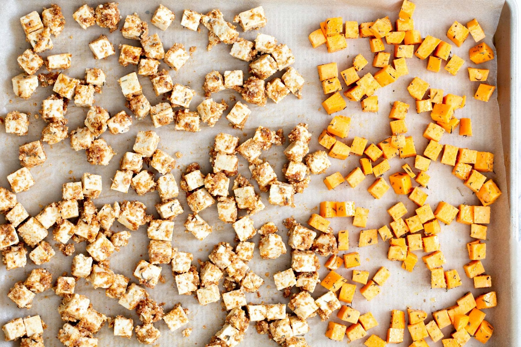 tofu and sweet potato cubes on a baking sheet ready to be baked