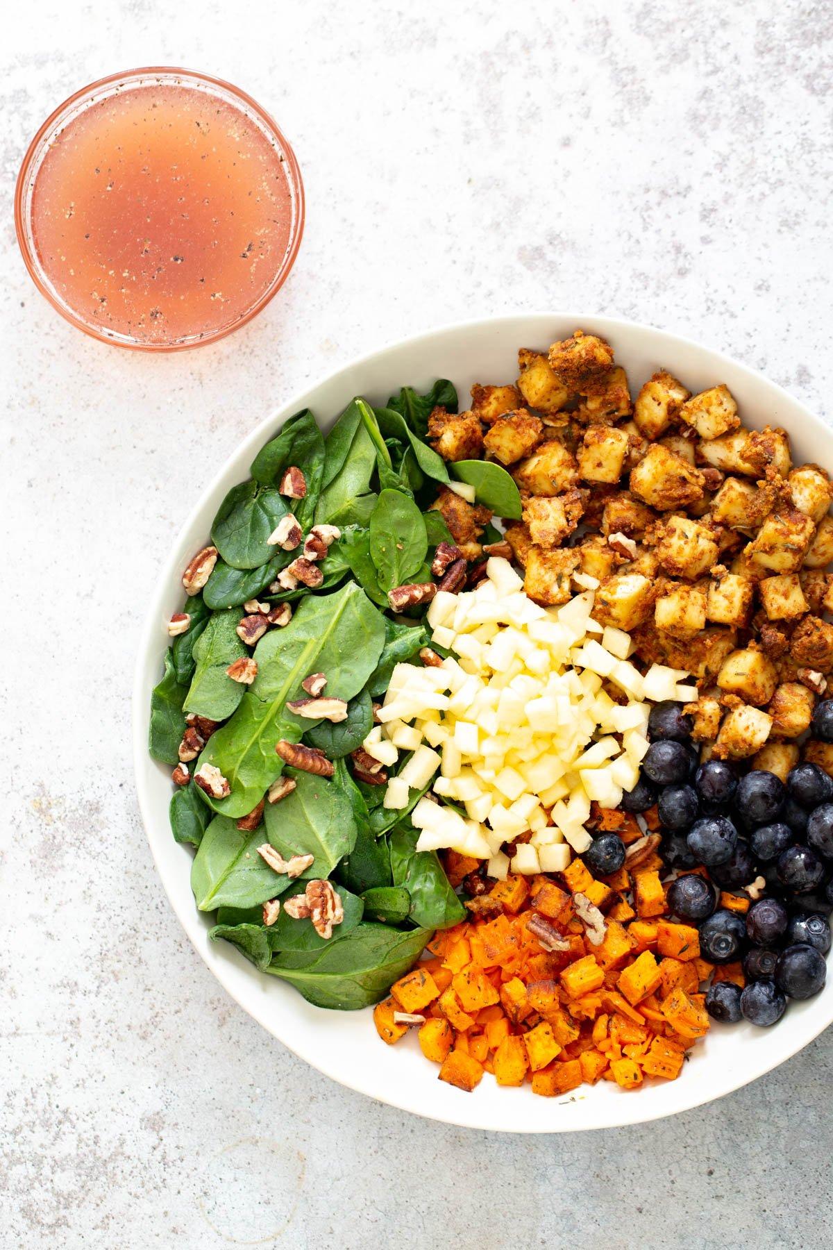 vegan sweet potato tofu bowl with a side of dressing