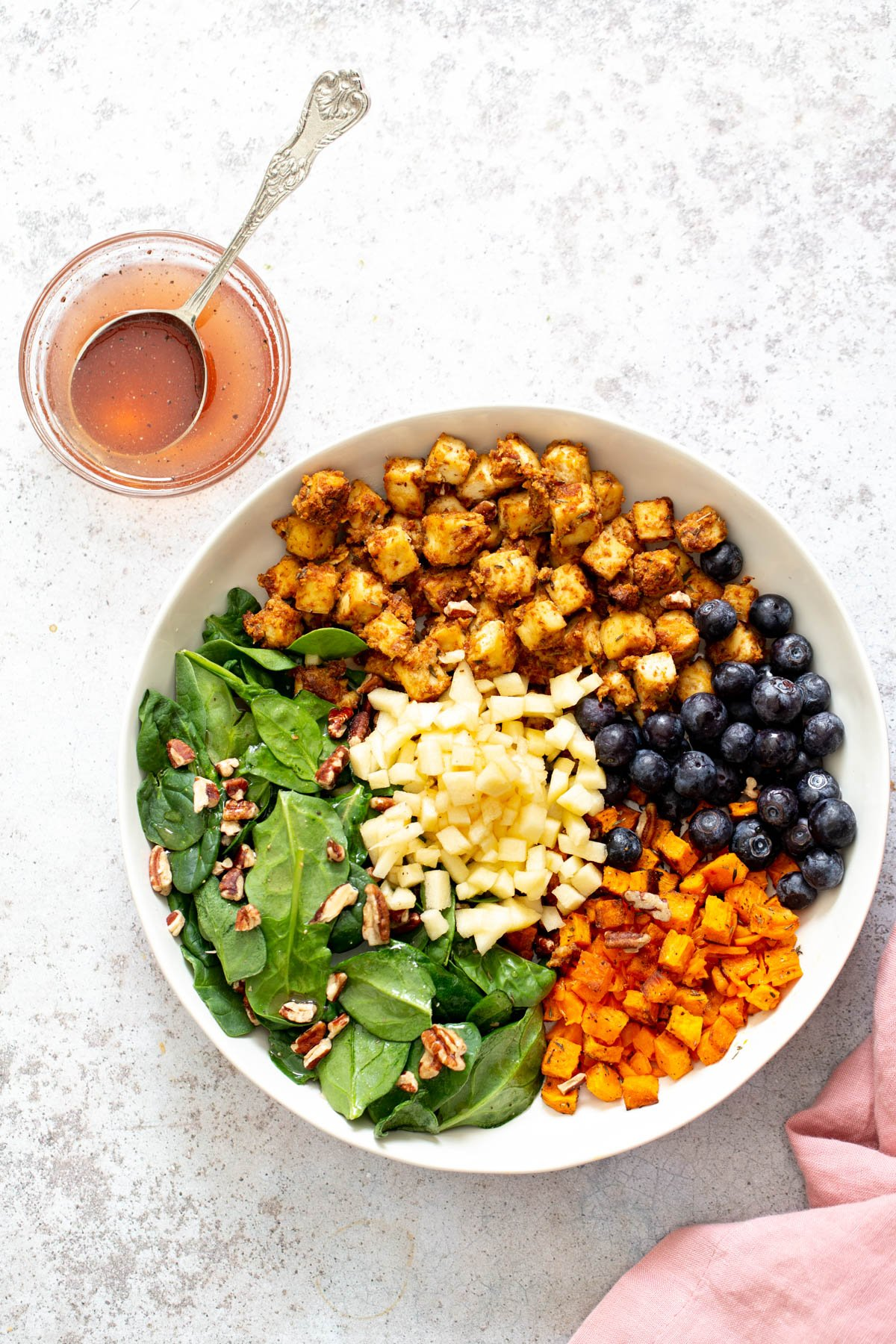 all ingredients for sweet potato tofu bowls assembled in a shallow white bowl with a side dish with dressing