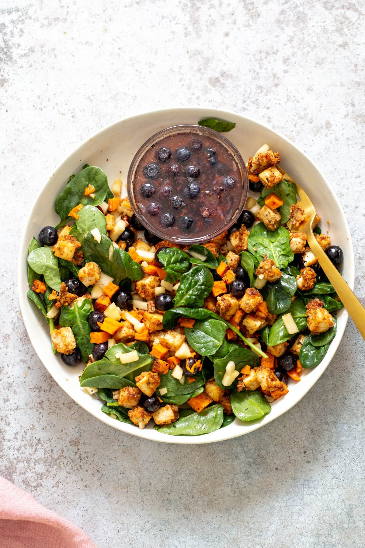 a bowl with baby spinach topped with baked sweet potatoes and crunchy tofu served with a small dish of maple blueberry dressing