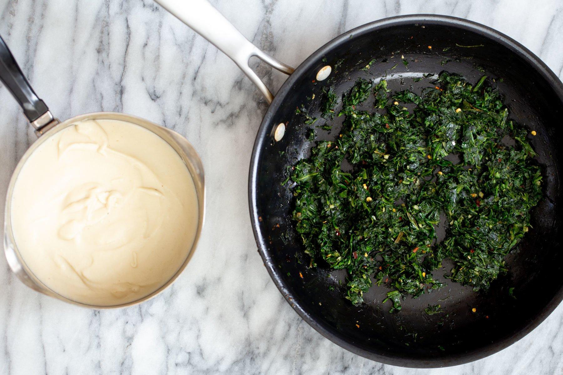 a pan with sauteed spinach next to a saucepan with vegan mozzarella cheese spread