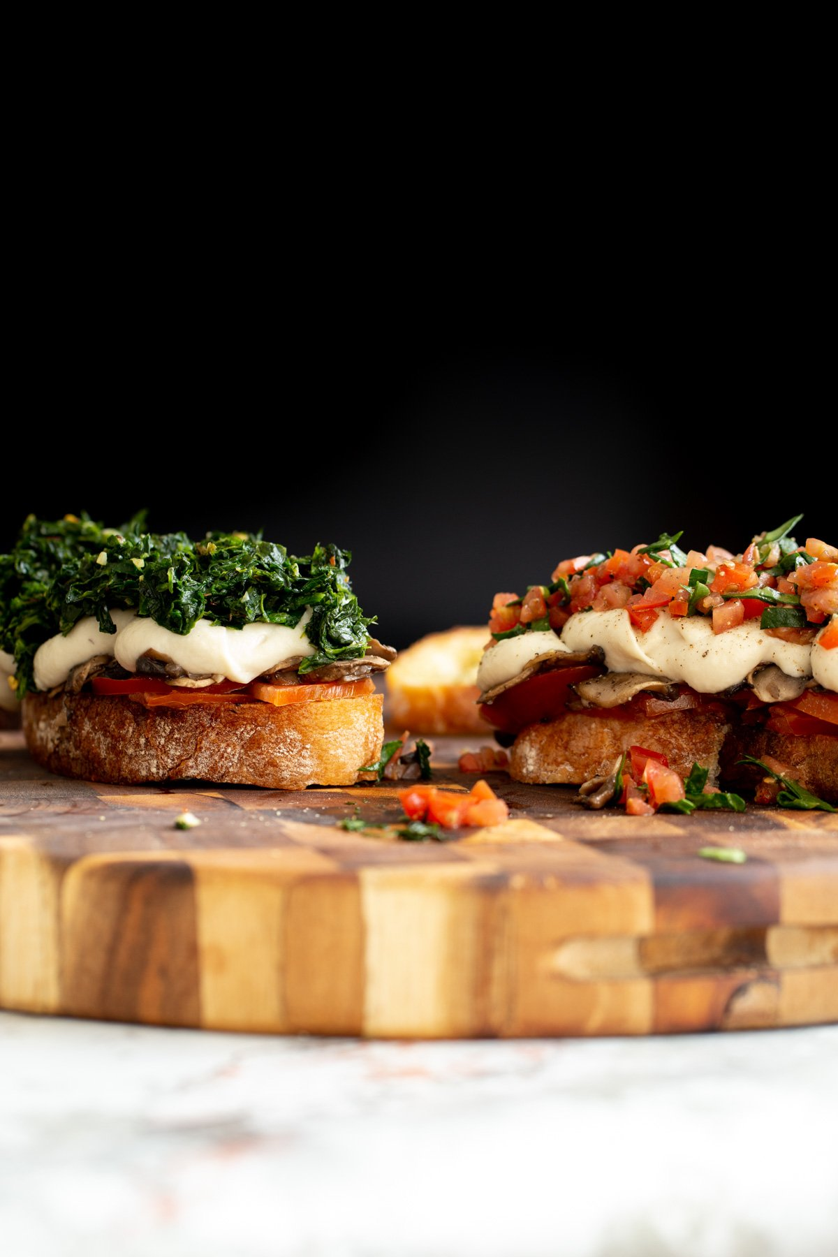 side view of vegan cheese melts topped with spinach and chopped tomatoes