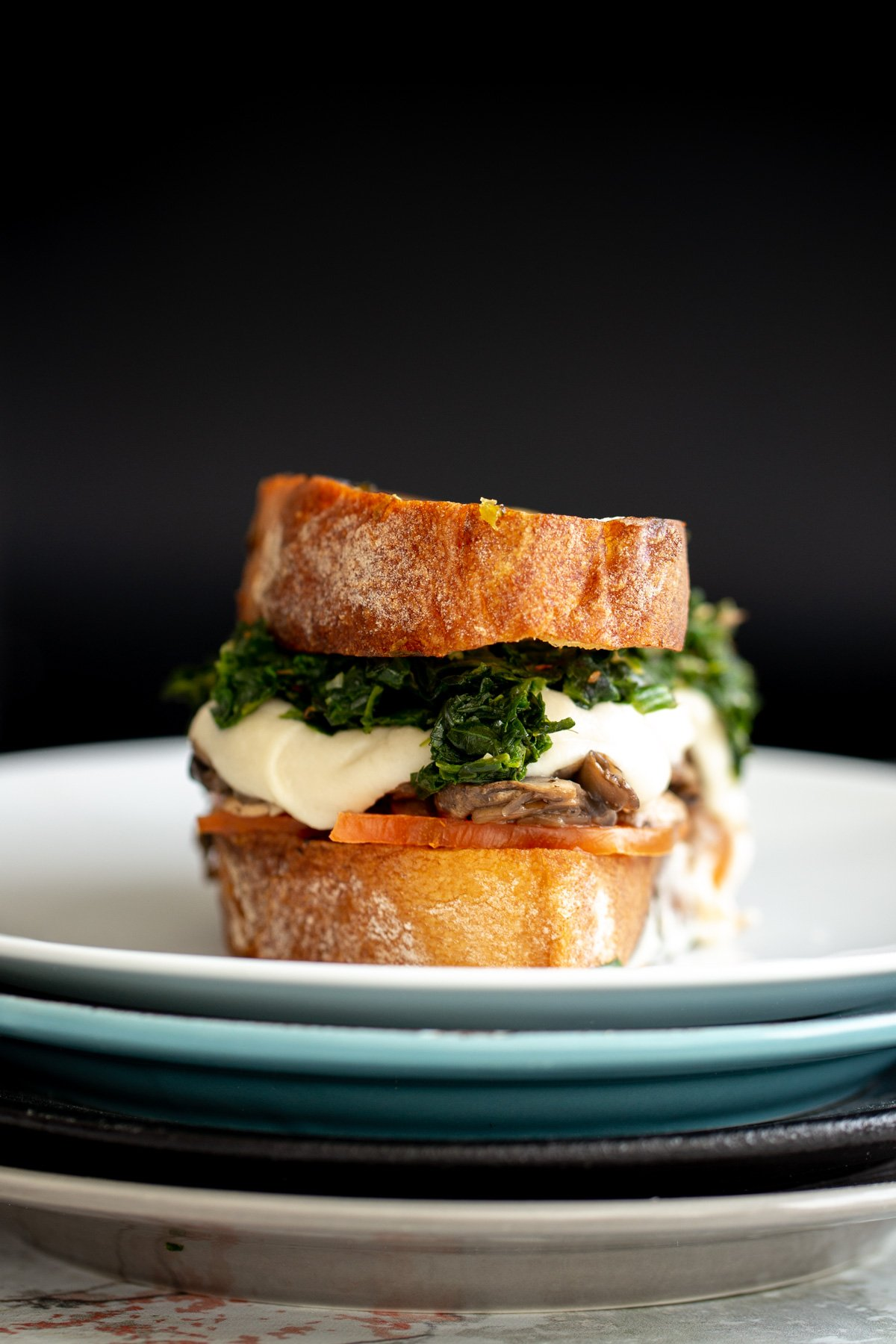 a vegan grilled cheese made with homemade cashew mozzarella , spinach and mushrooms