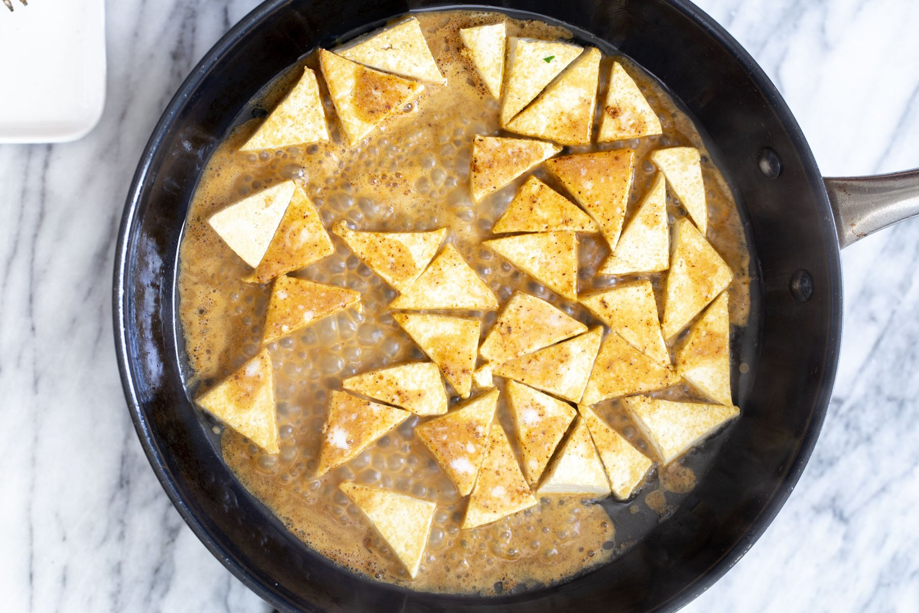 curry sauce being added to saucepan to coat pan-fried tofu