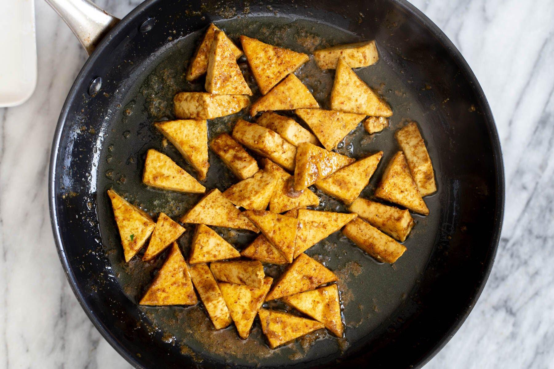 pan-fried curried tofu in a black skillet