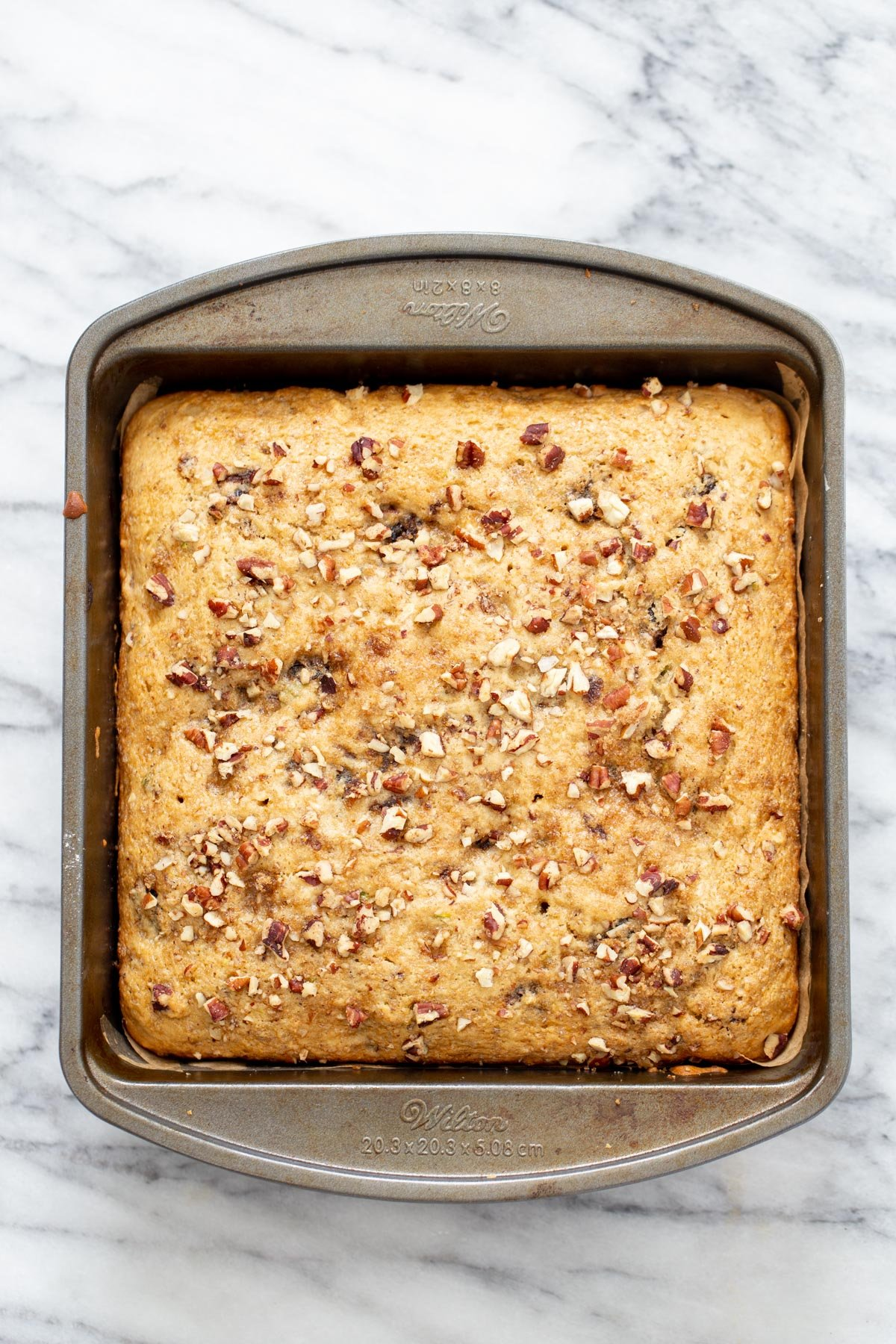 overhead shot of a vegan date nut cake in a cake pan on a marble countertop