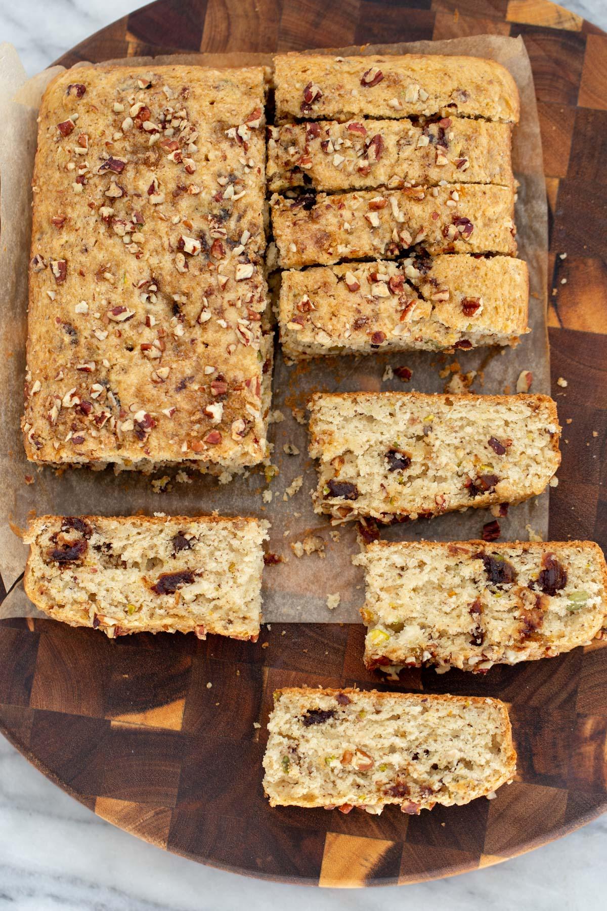 vegan date nut cake cut on a wooden chopping board
