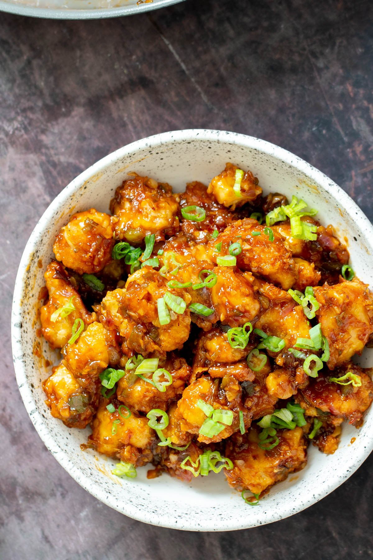 a white bowl with vegan gobi Manchurian topped with thinly sliced scallions
