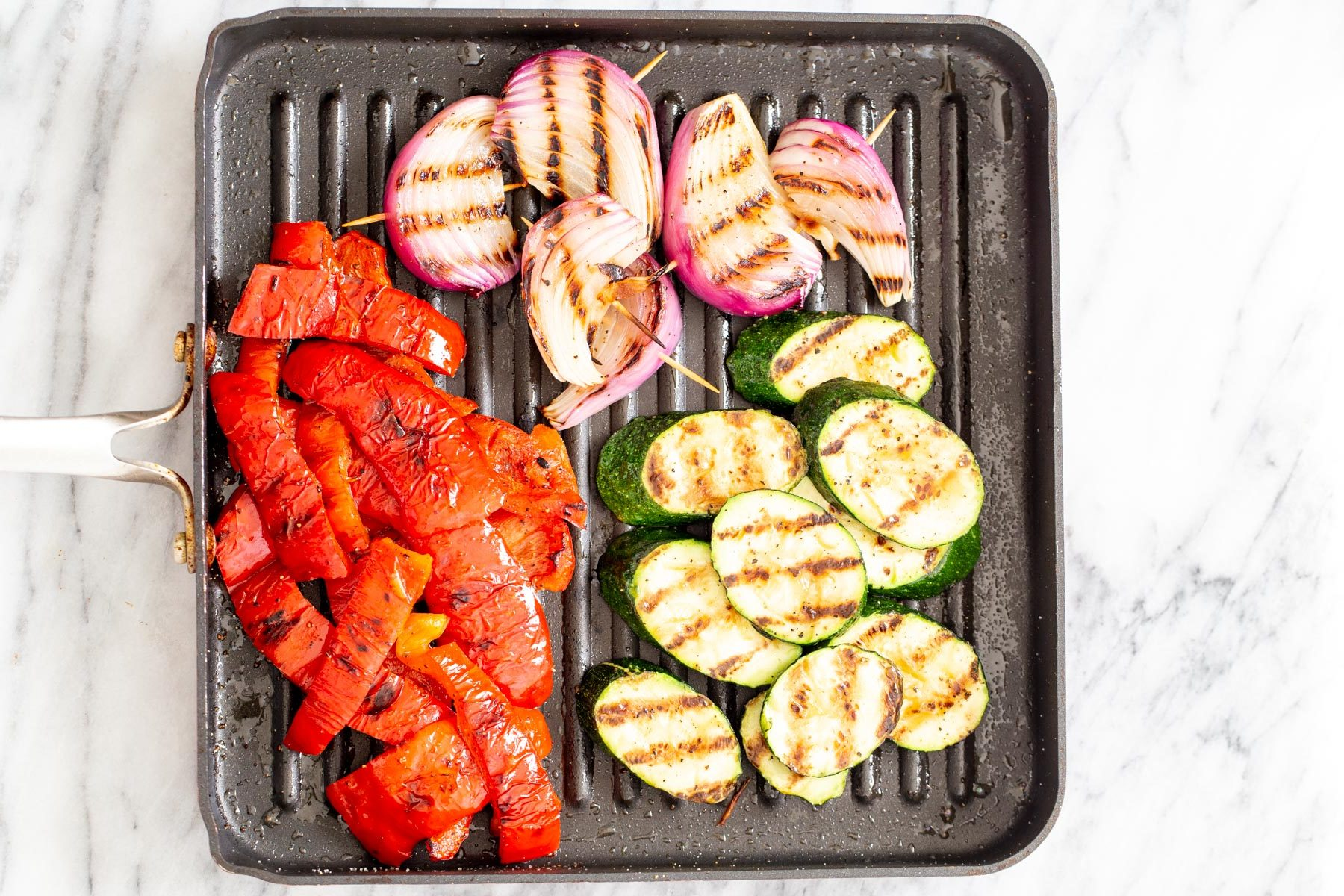 grilled bell pepper, zucchini and onion wedges in a black grill pan