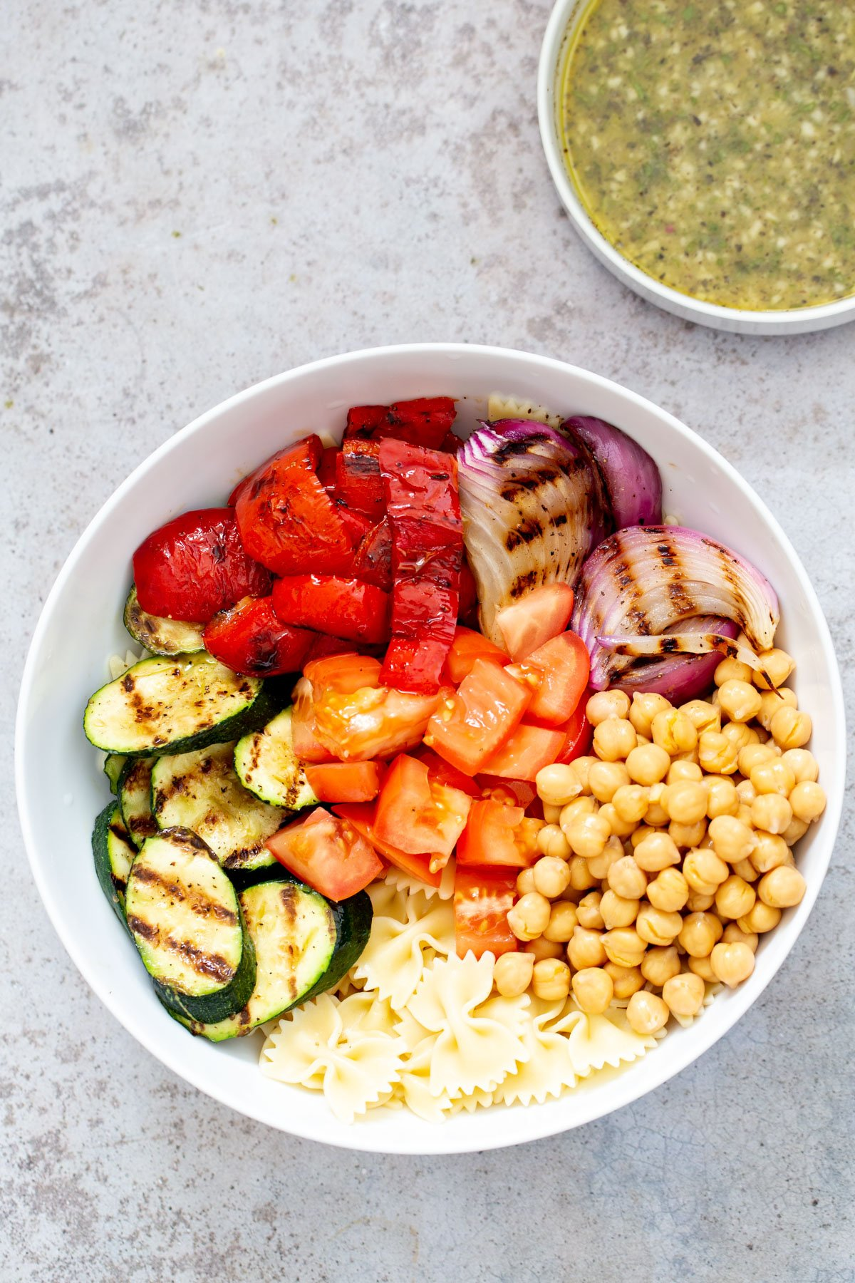 ingredients for vegan pasta salad with grilled vegetables and chickpeas all arranged in a bowl with a dish with dressing on the side