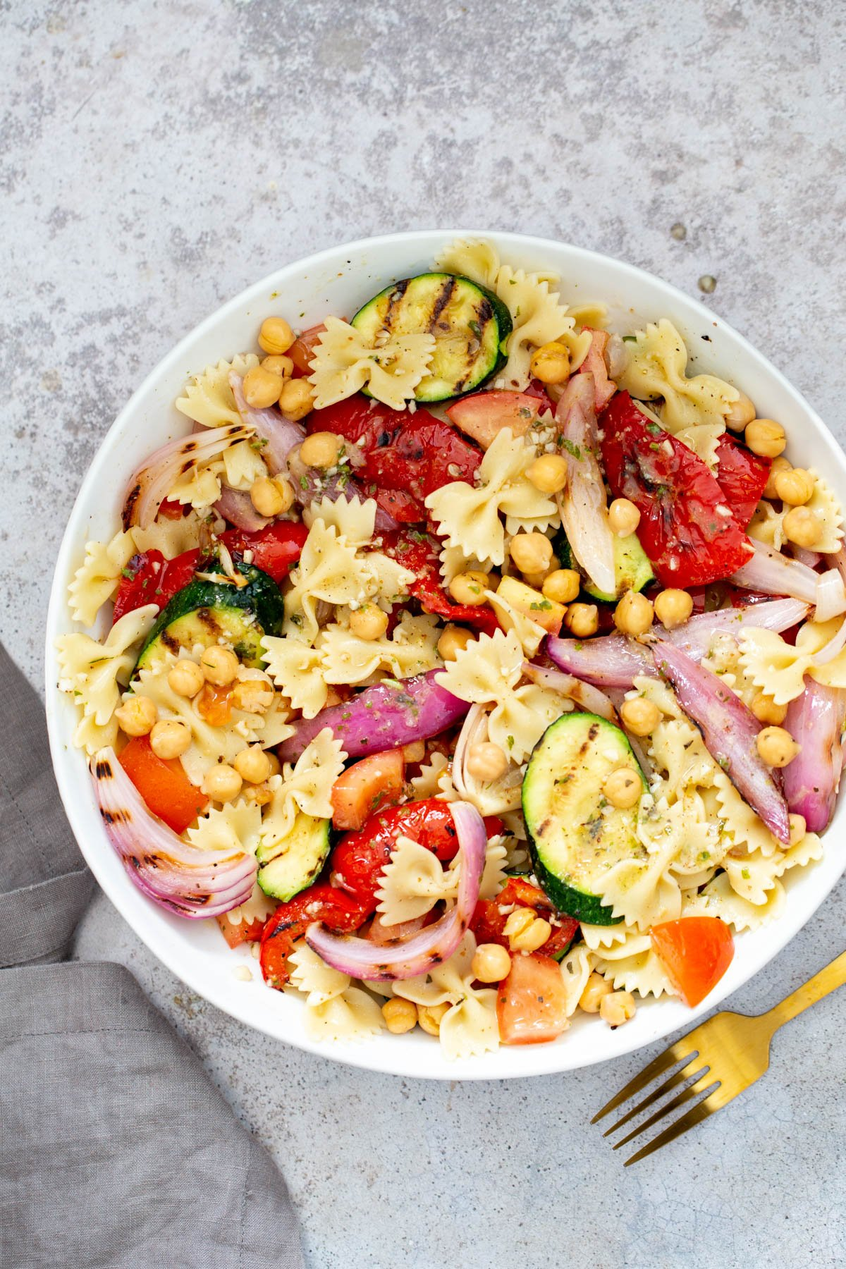 vegan grilled vegetable pasta salad with chickpeas served on a white plate with a golden fork and a cloth napkin on the side