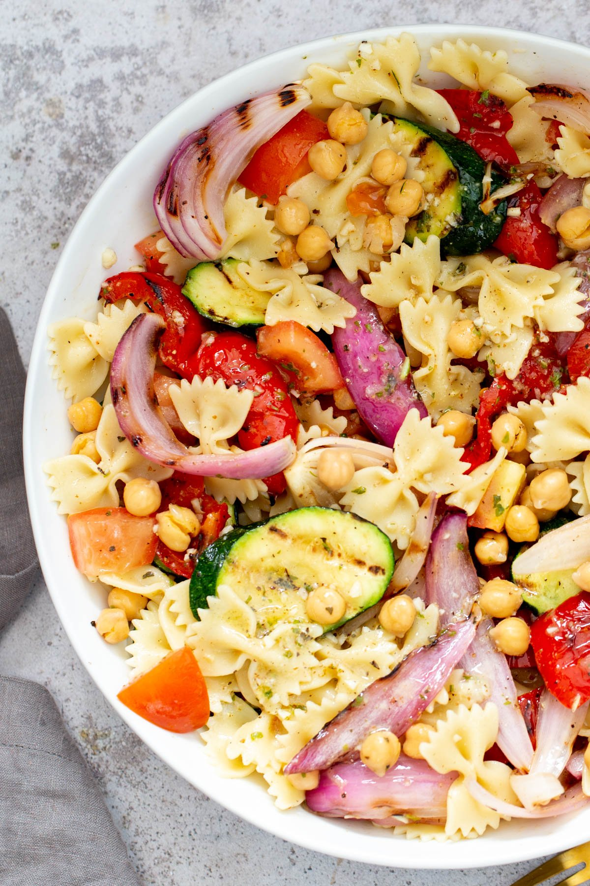 a bowl of vegan pasta salad with grilled vegetables, tomatoes and chickpeas