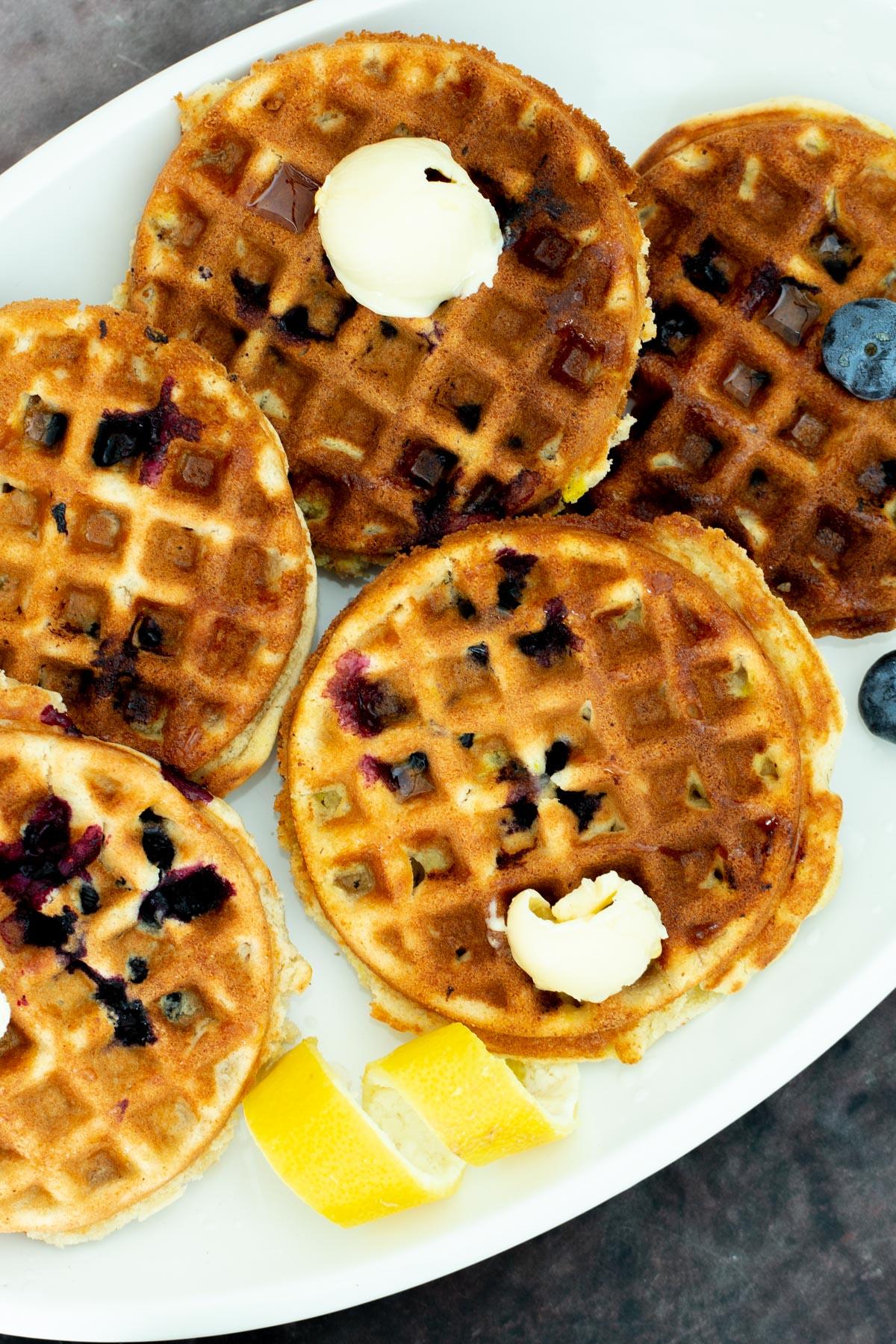 vegan glutenfree Lemon Blueberry Waffles on a platter served with dollops of butter