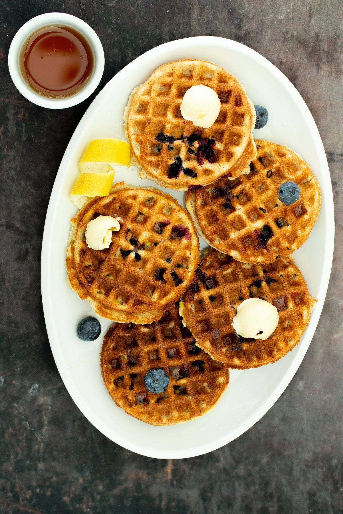 a white platter with glutenfree vegan lemon blueberry waffles served with a side dish of maple syrup