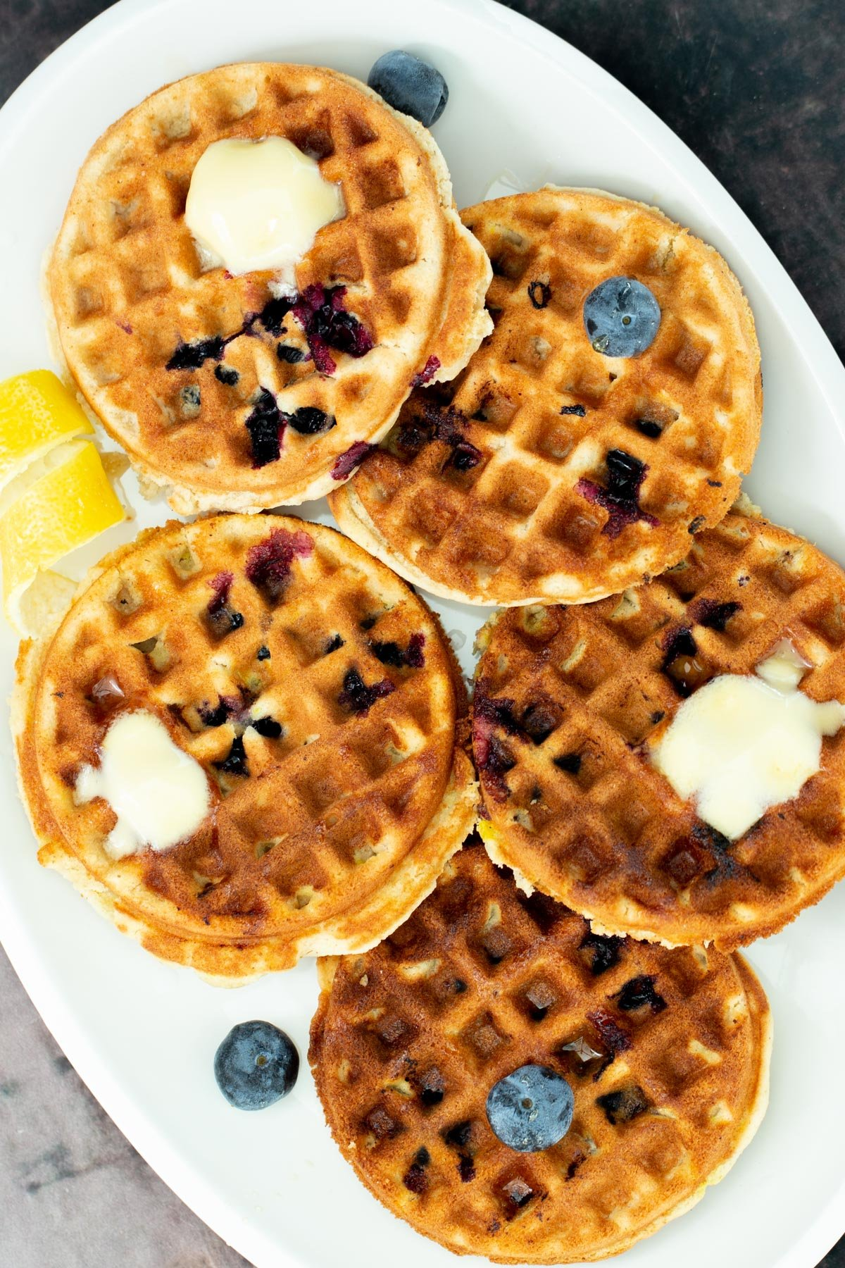 a plate of vegan glutenfree lemon blueberry waffles topped with dollops of butter and fresh blueberries