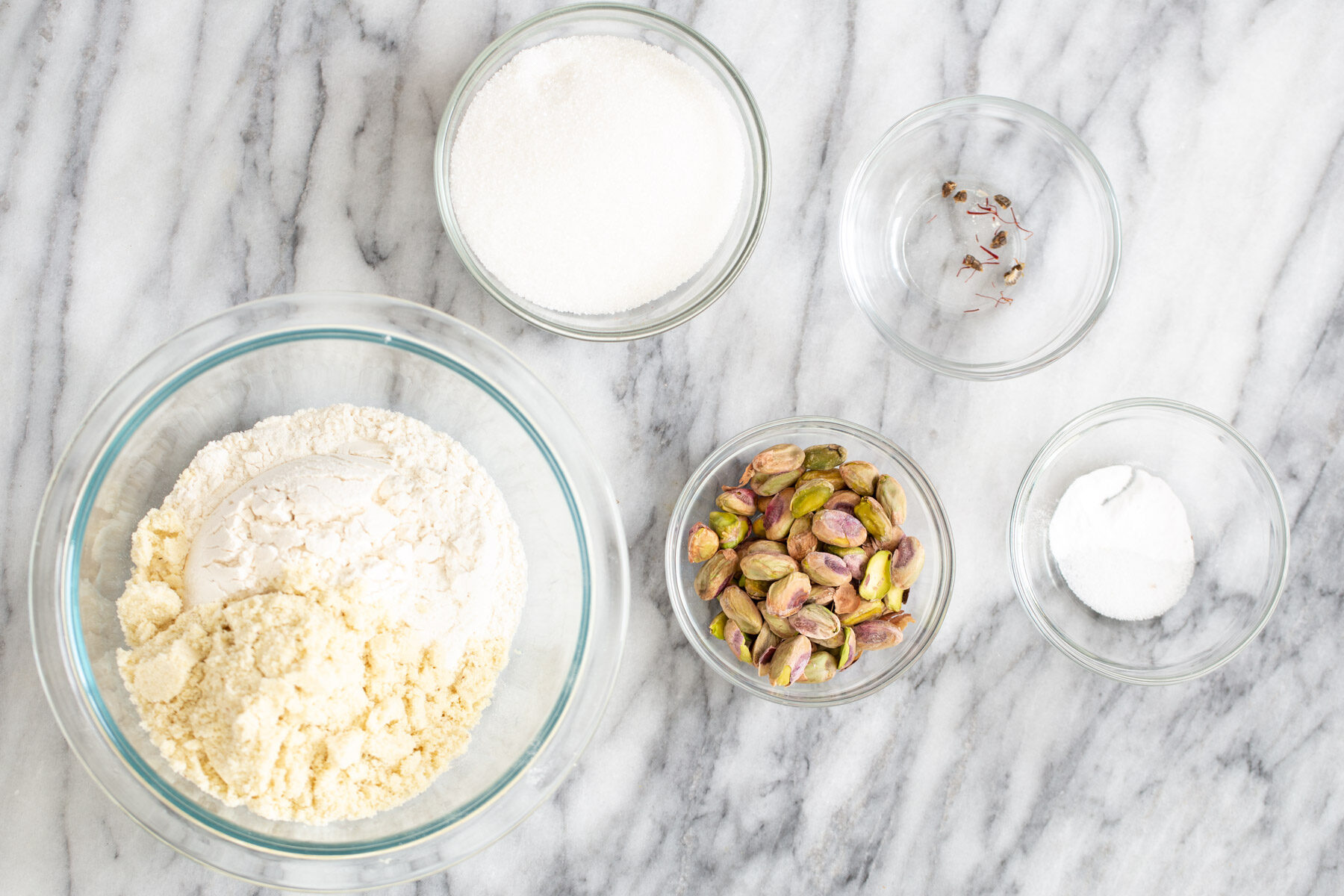 ingredients for vegan pistachio cookie recipe on a marble kitchen counter