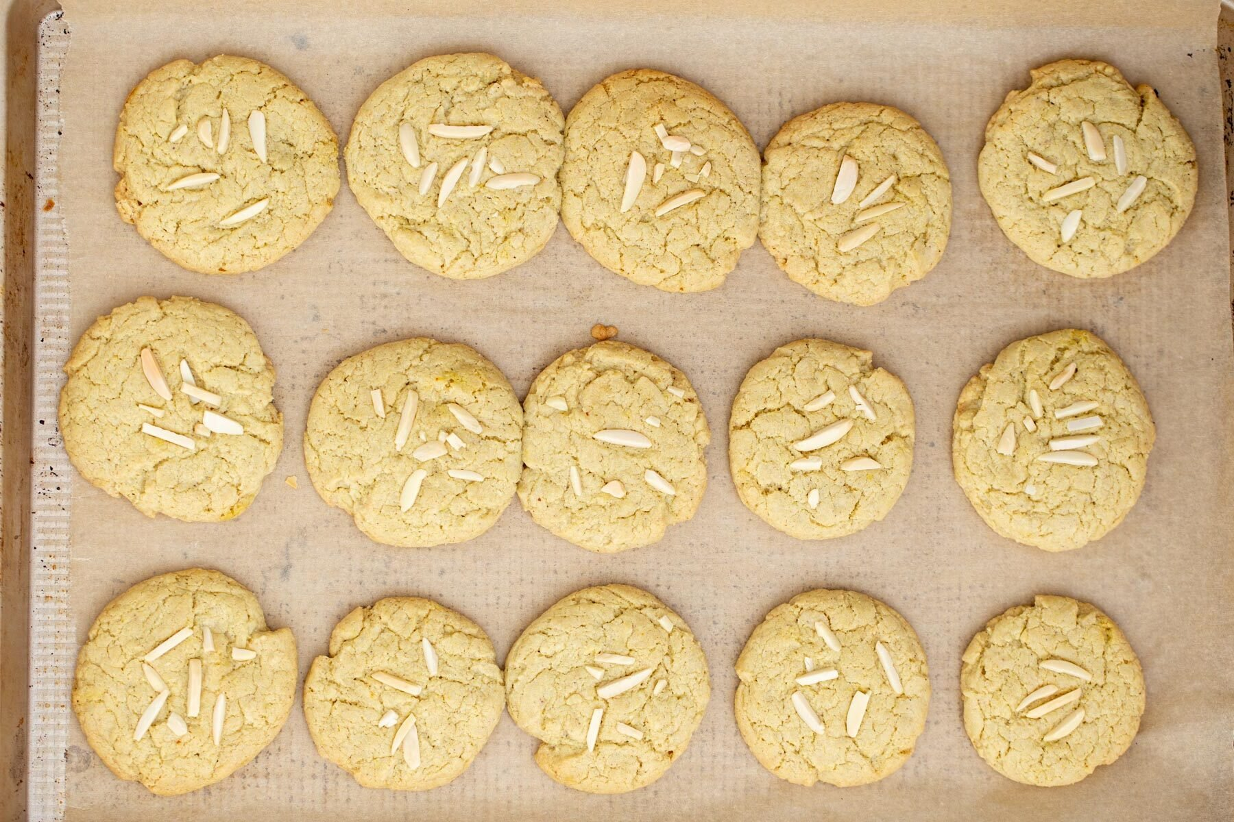 freshly baked vegan pistachio cookies on a lined sheet pan