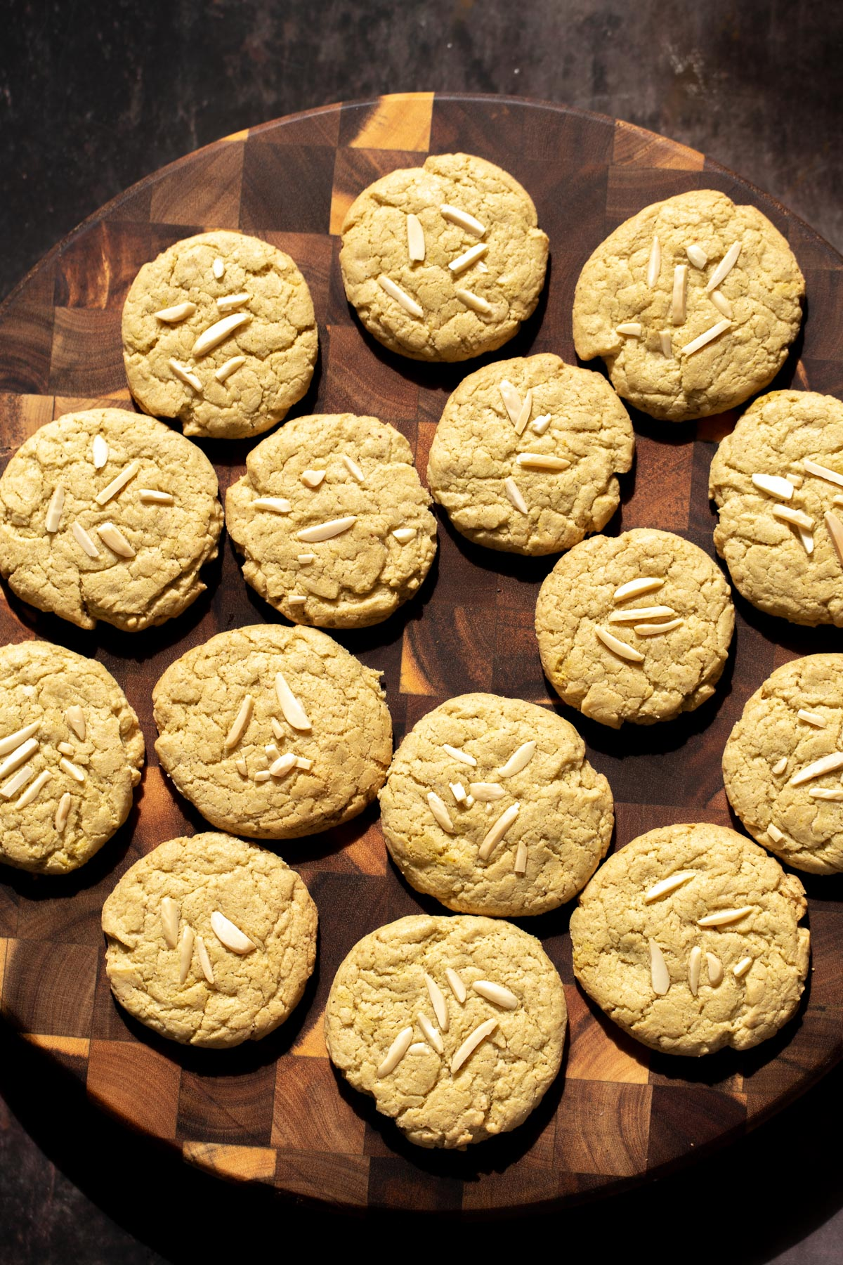 vegan pistachio cookies decorated with almond slivers on a wooden board
