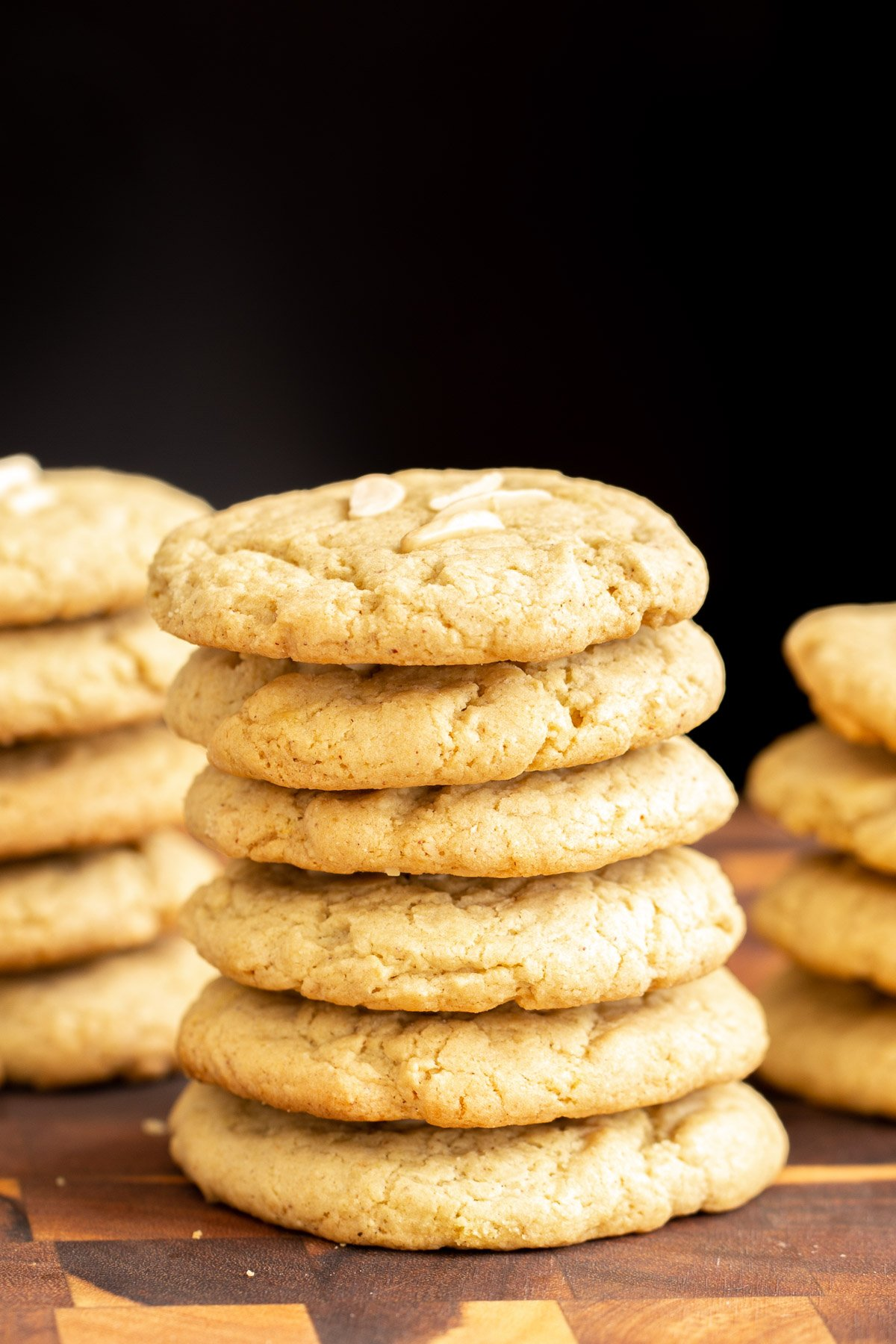 side view of a stack of vegan almond pistachio cookies on a wooden board