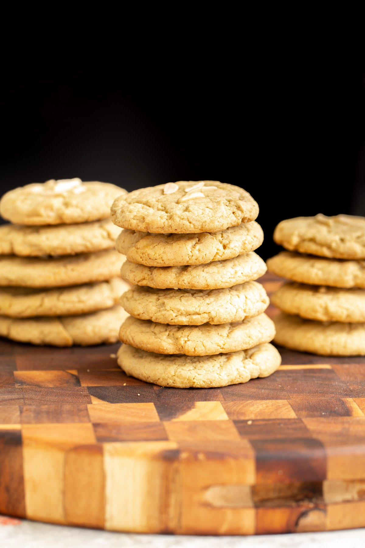 stacked vegan almond flour pistachio cookies topped with slivered almonds on a wooden chopping board